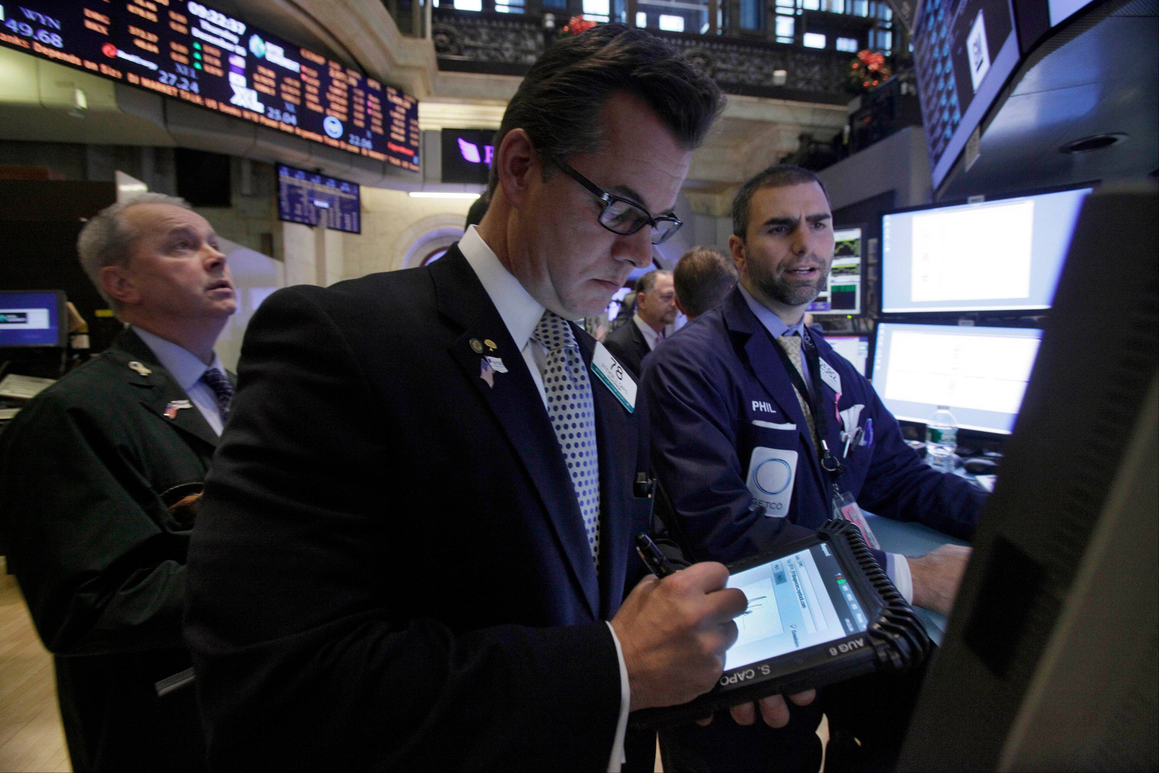 Trader Steven Capo, center, works on the floor of the New York Stock Exchange Thursday.
