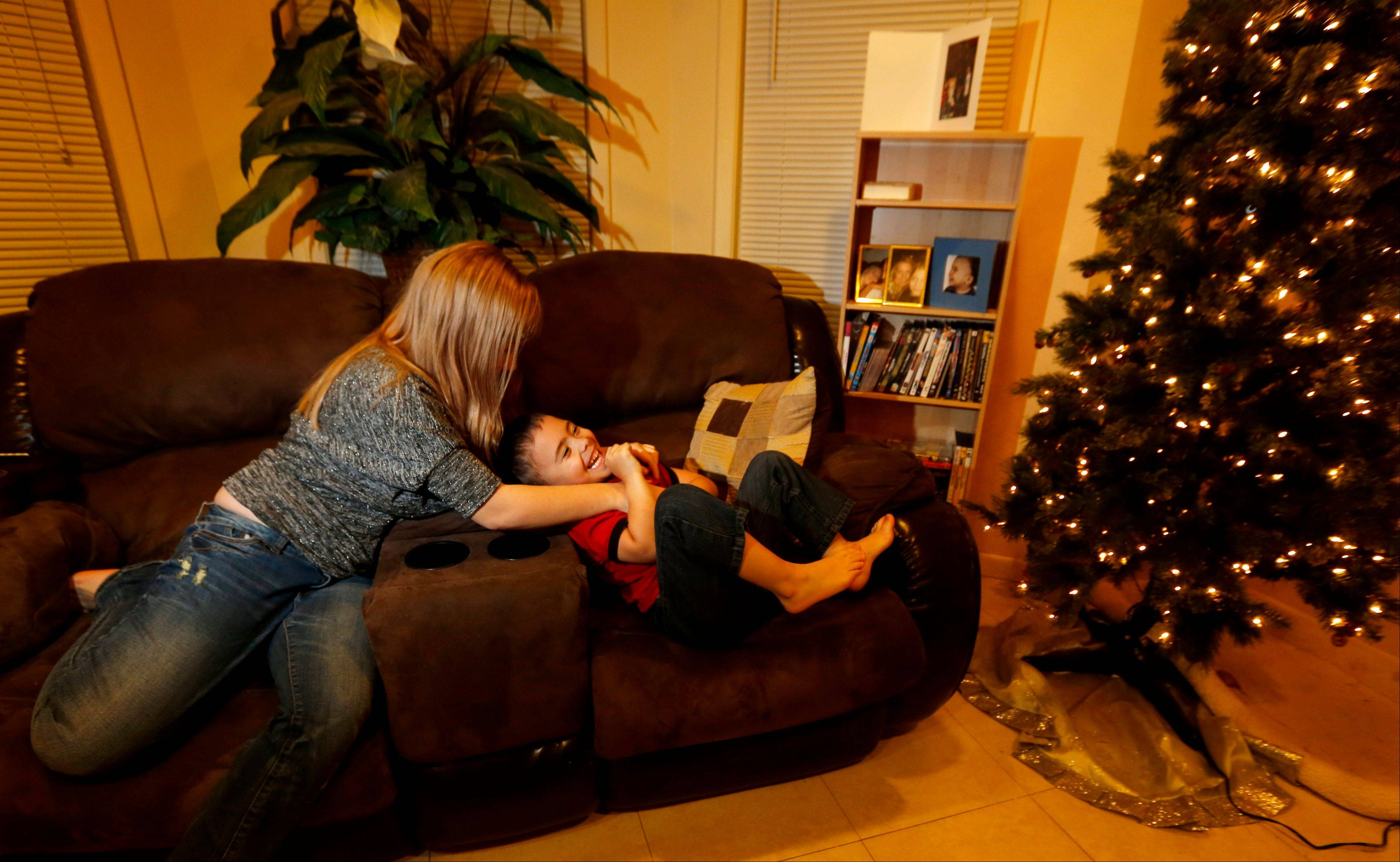 McKenna Pope, 13, left, plays with her brother Gavyn Boscio, 4, in their home Thursday in Garfield, N.J.