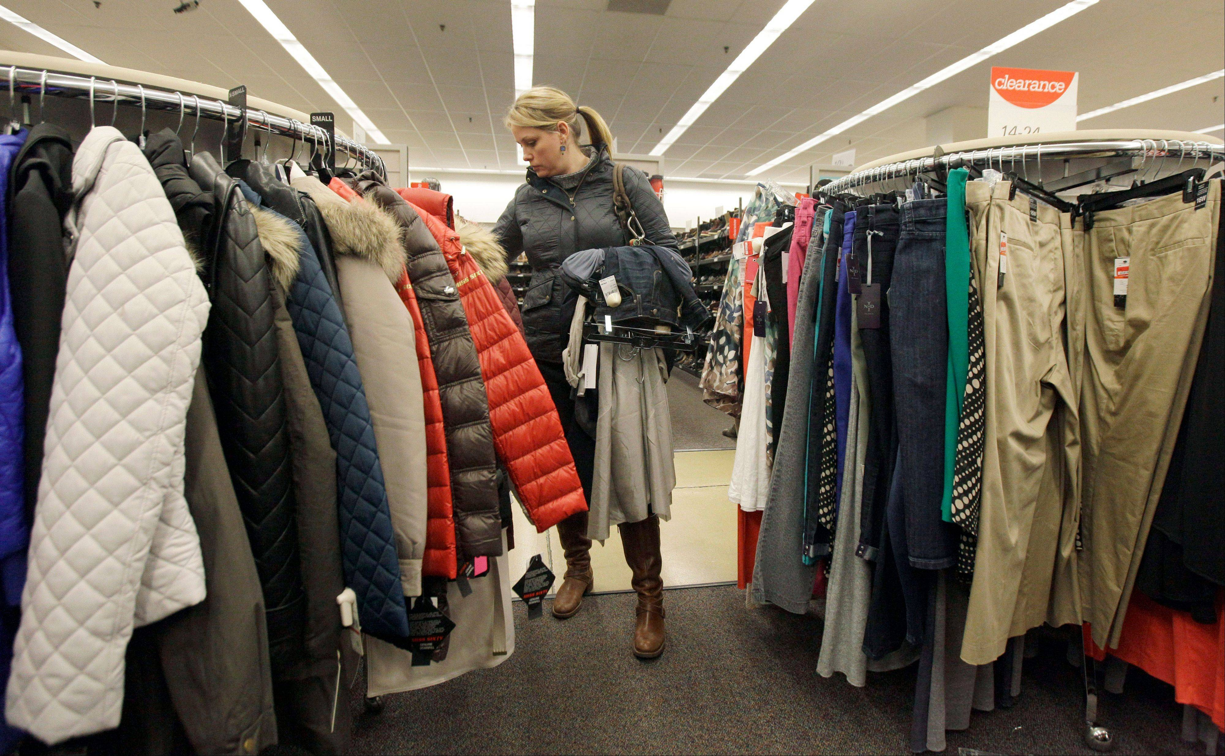 Associated Press/Nov. 1, 2012 A shopper checks winter jackets in a Nordstrom rack in Chicago.