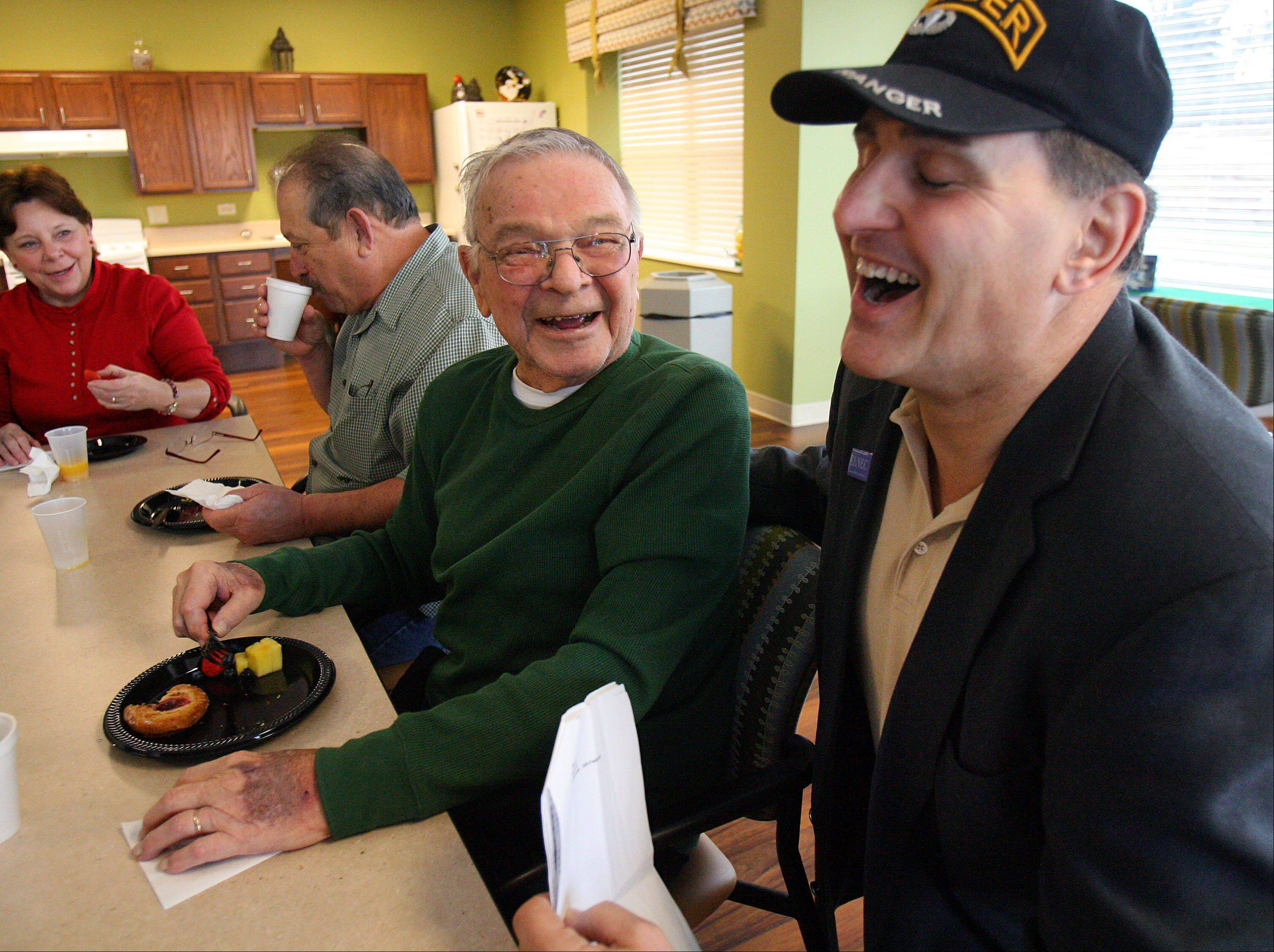 World War II veteran and resident of Oak Hill Supportive Living Richard Siver, left, has a laugh with presenter Andy Balafas of Vitas Innovative Hospice Care during a Pearl Harbor Day event to honor area veterans Friday in Round Lake Beach.