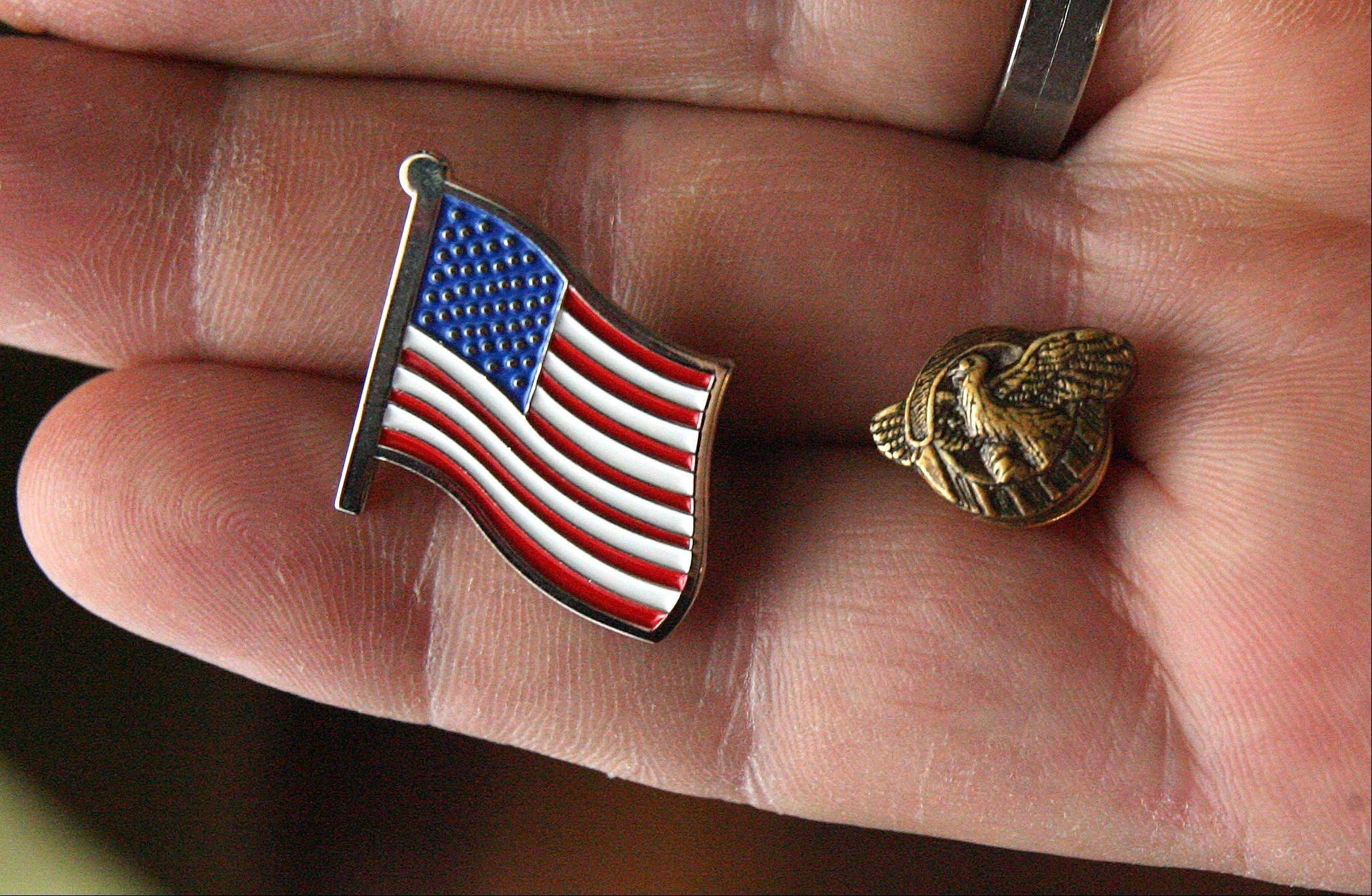 "Pins were given out to veterans during a Pearl Harbor Day event to honor area veterans at Oak Hill Supportive Living Friday in Round Lake Beach. The pin on the right is called the ""Ruptured Duck"" and is a World War II honorable discharge pin. Other vets received a flag pin."