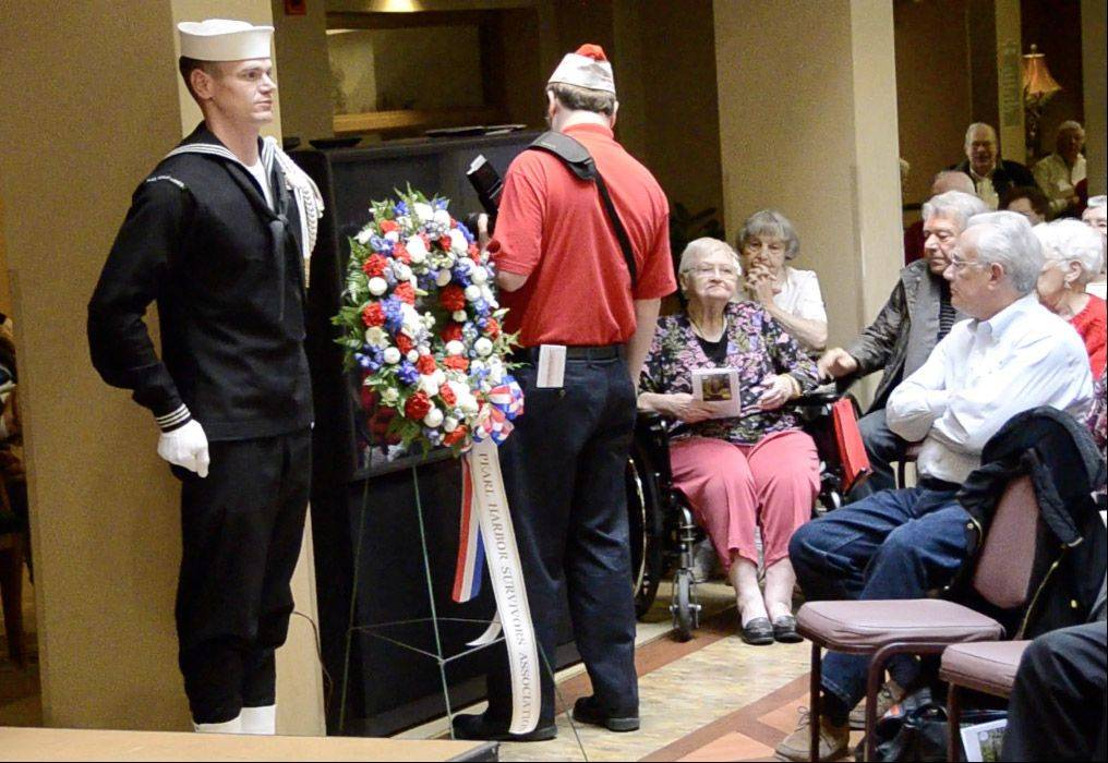 "A sailor stands at attention after placing a wreath while the Navy Band plays the ""The Naval Hymn"" at a Pearl Harbor remembrance ceremony at Oakton Place retirement home in Des Plaines."