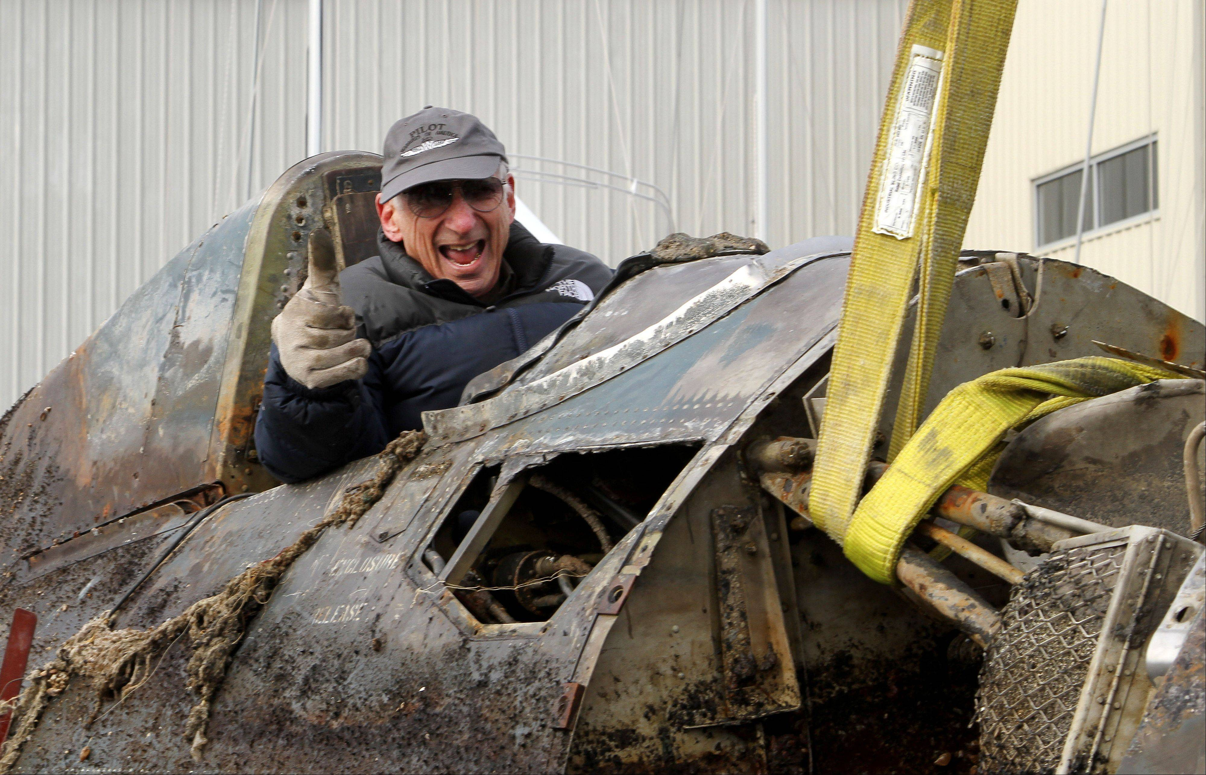 Chuck Greenhill of Mettawa is the first person to sit in the cockpit of this World War II era FM-2 Wildcat after it was pulled out of the water at Larsen Marine in Waukegan Friday. Greenhill helped sponsor the salvage effort.