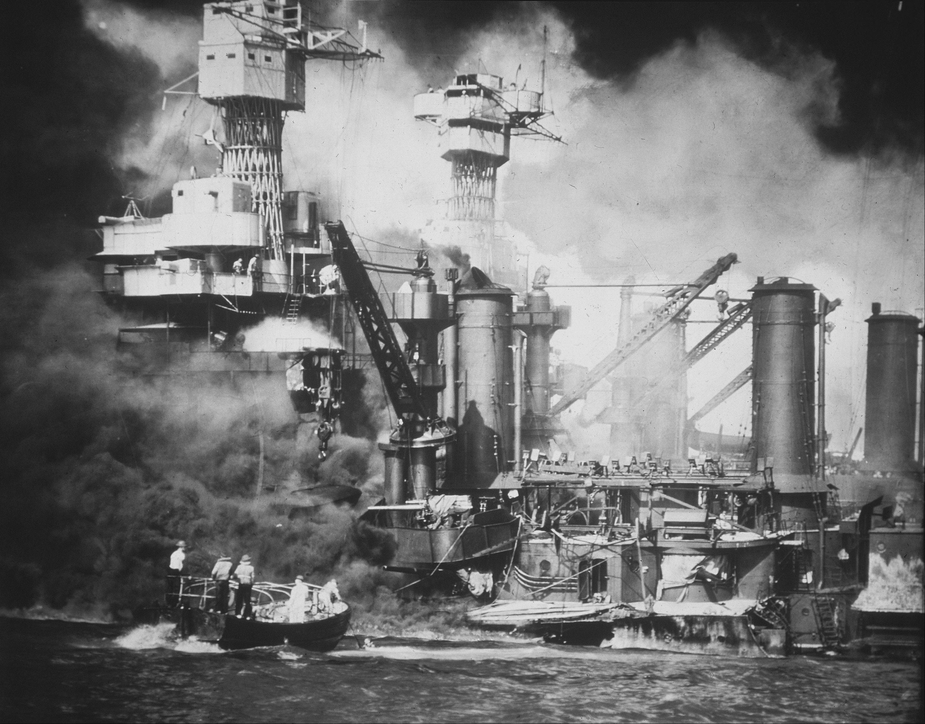 In this U.S. Navy file photo, a small boat rescues a USS West Virginia crew member from the water after the Japanese bombing of Pearl Harbor, Hawaii on Dec. 7, 1941 during World War II. Two men can be seen on the superstructure, upper center. The mast of the USS Tennessee is beyond the burning West Virginia.