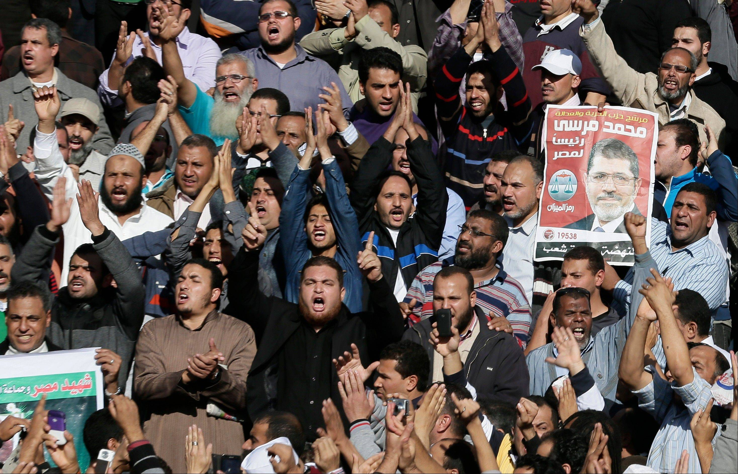"Supporters of Muslim Brotherhood and Egyptian President Mohammed Morsi, pictured at right, chant slogans during the funeral of three victims who were killed during Wednesday's clashes outside Al-Azhar mosque, the highest Islamic Sunni institution, Friday, Dec. 7, 2012. During the funeral, thousands Islamist mourners chanted, ""with blood and soul, we redeem Islam,"" pumping their fists in the air. ""Egypt is Islamic, it will not be secular, it will not be liberal,"" they chanted as they walked in a funeral procession that filled streets around Al-Azhar mosque."