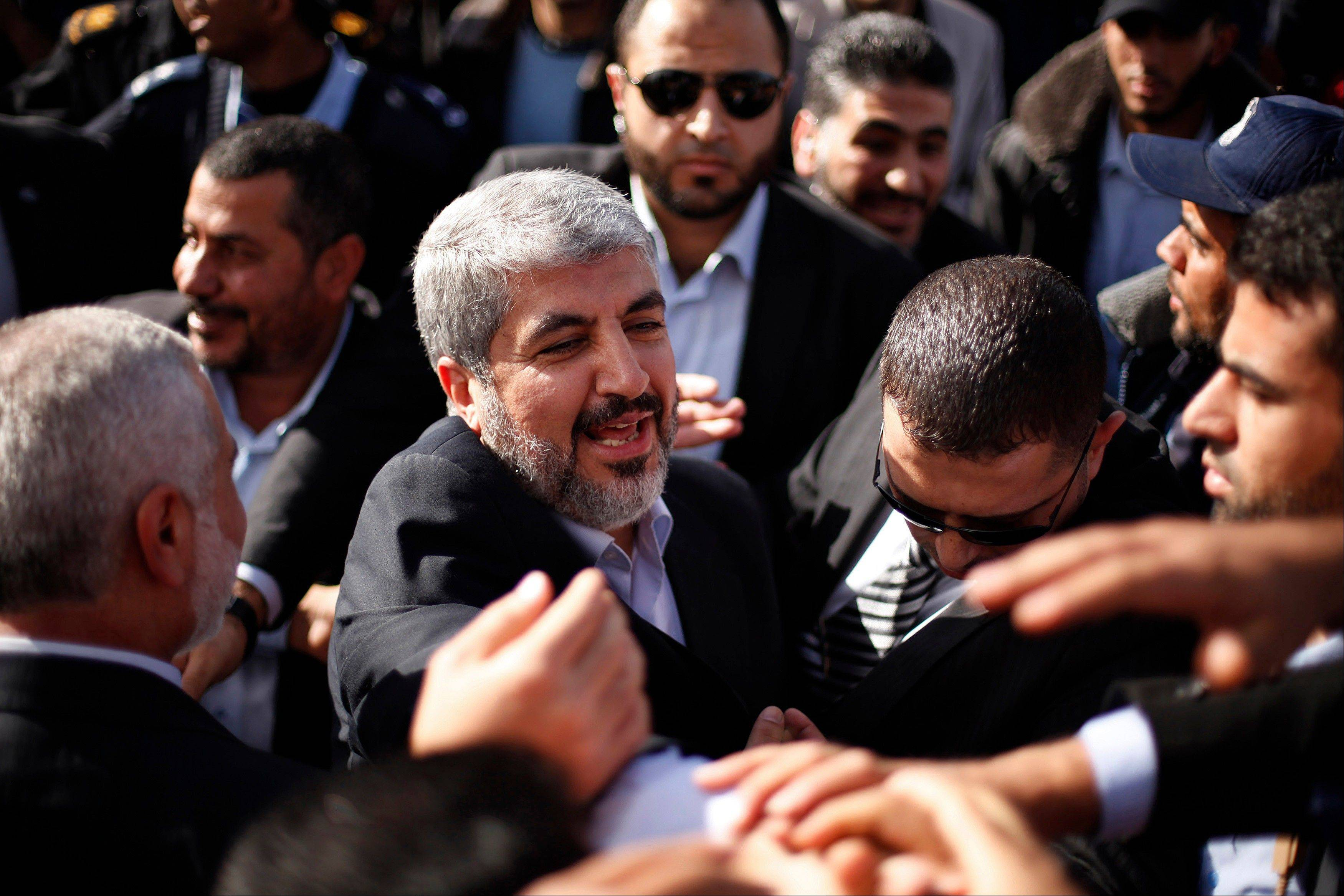 The exiled Hamas chief Khaled Mashaal shakes hands with supporters upon his arrival at Rafah crossing in the southern Gaza Strip, Friday, Dec. 7, 2012. Mashaal broke into tears Friday as he arrived in the Gaza Strip for his first-ever visit, a landmark trip reflecting his militant group's growing international acceptance and its defiance of Israel.