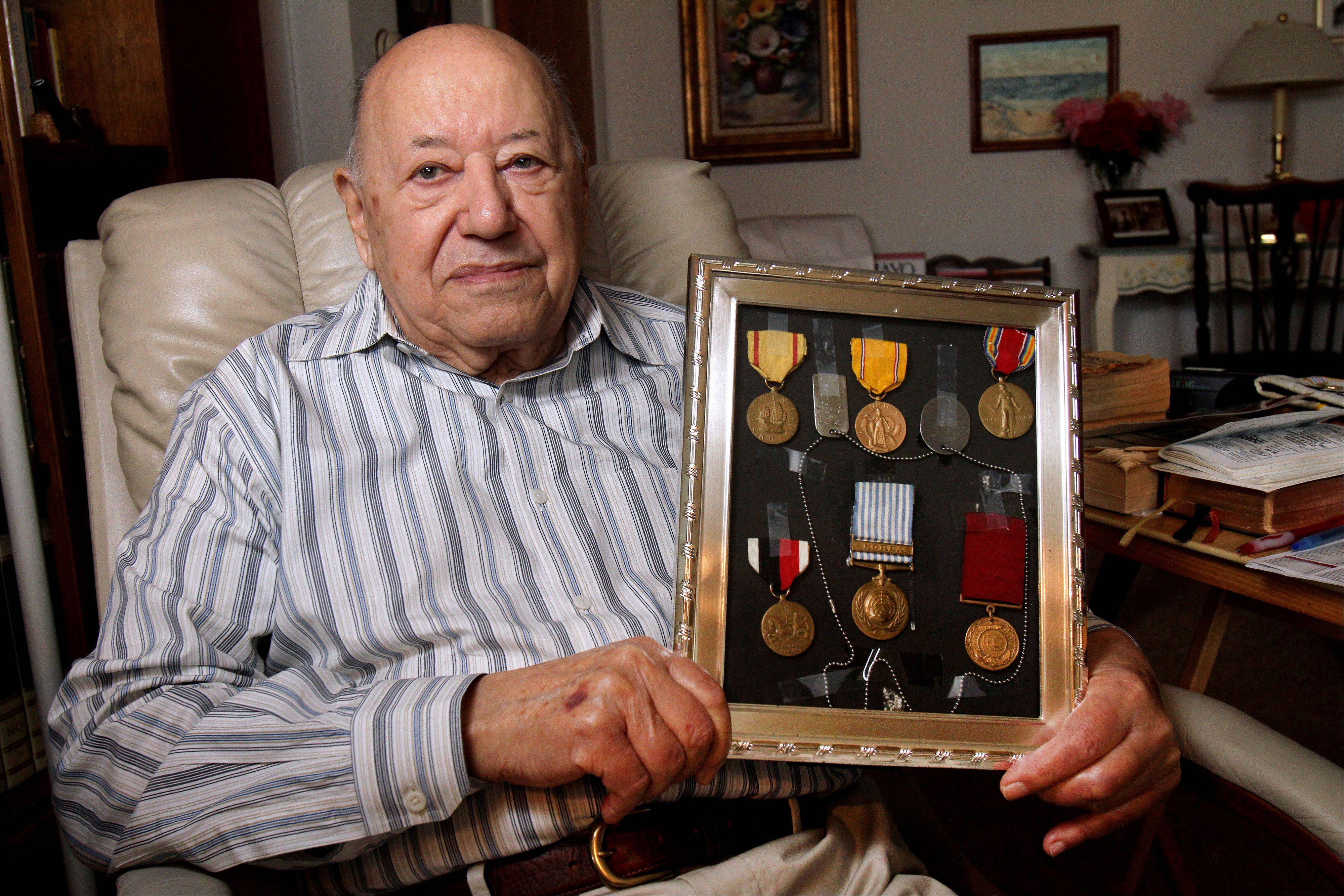 Pearl Harbor attack survivor Joe Triolo, 92, of Waukegan holds medals he earned while serving in World War II and Korea. Triolo will be on hand today at a Des Plaines event commemorating the 71st anniversary of the attack.