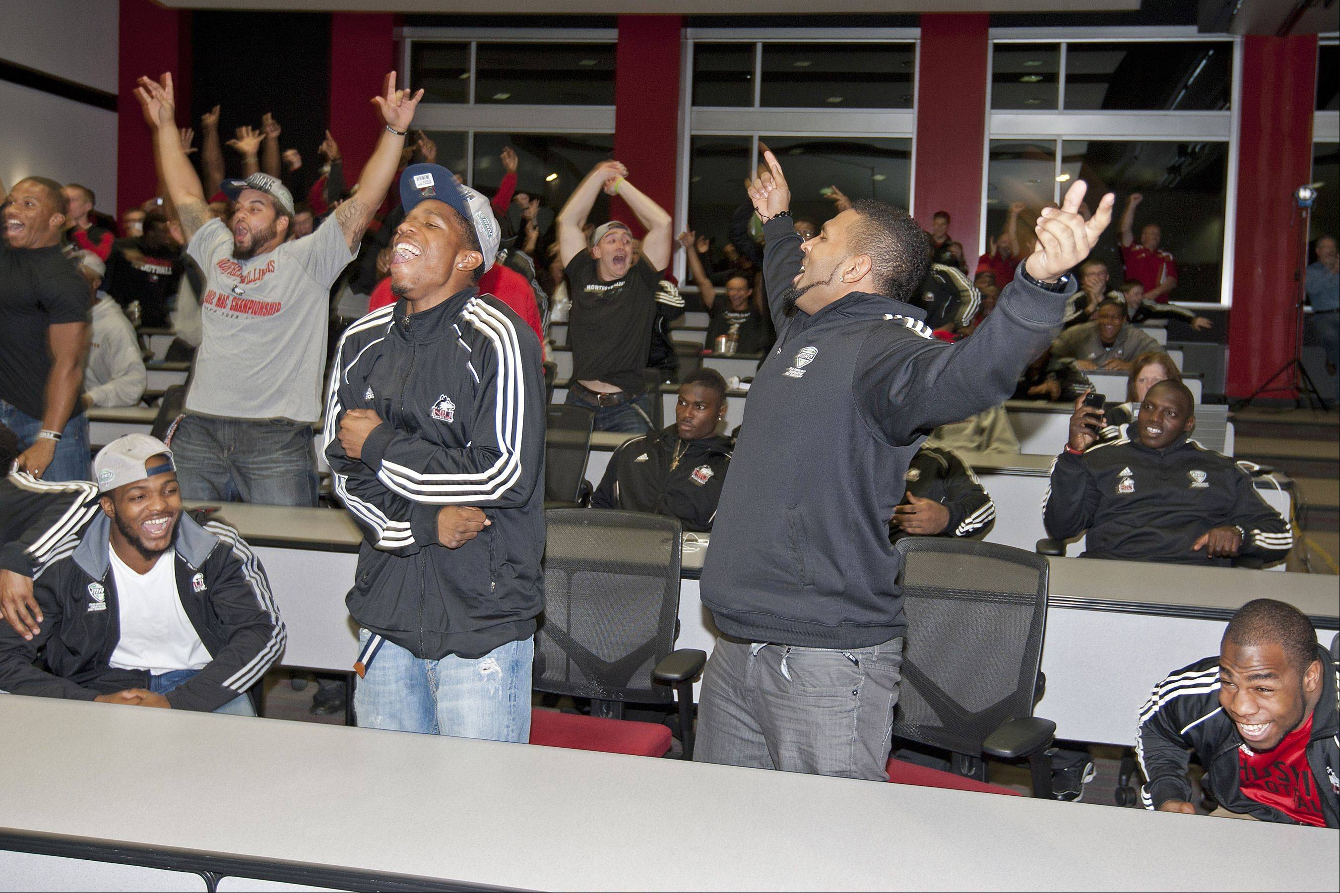 Football team members react on Sunday night during a press conference in DeKalb as the NIU Huskies learned of their Orange Bowl berth.