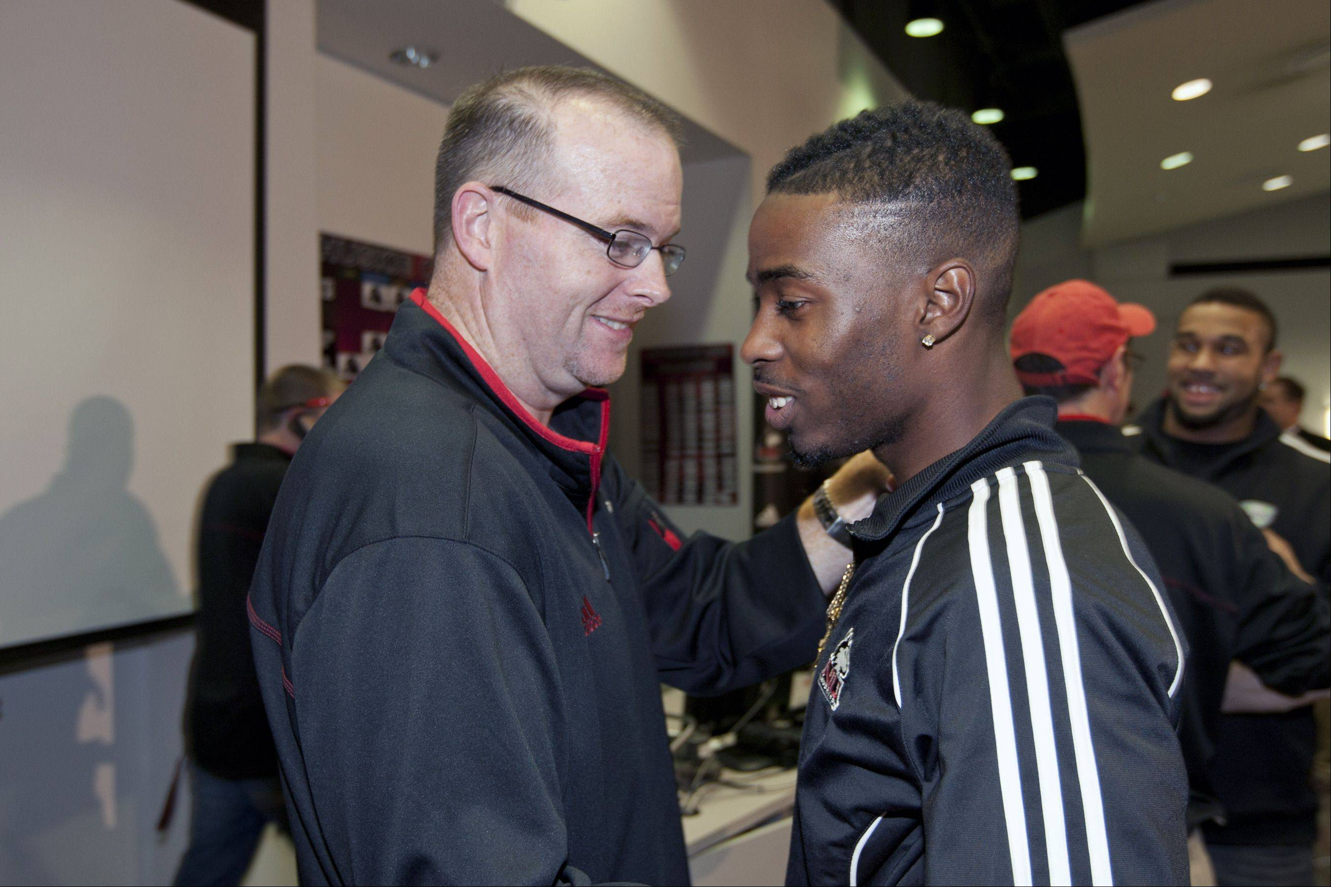 Coach Carey and Martel Moore react in DeKalb as the NIU Huskies learned of their Orange Bowl berth Sunday night.