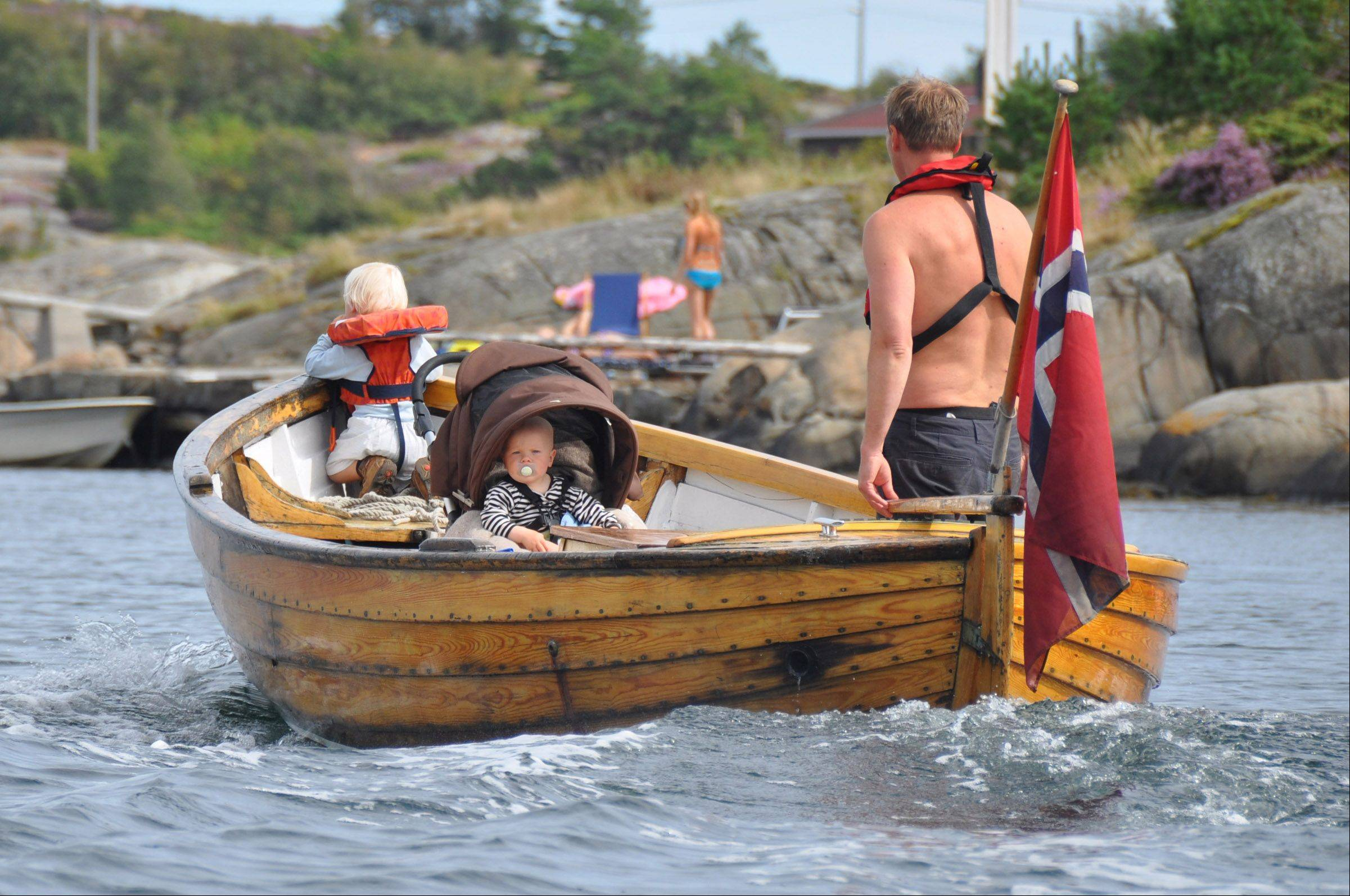 This is a photo I took this summer while traveling with my mother in the Lyngor Fiord, Norway. We crossed by this boat going in the opposite direction and I had just a second or two to get the shot. I LOVE the dichotomy of the modern father shuttling his children in an ancient wooden boat!
