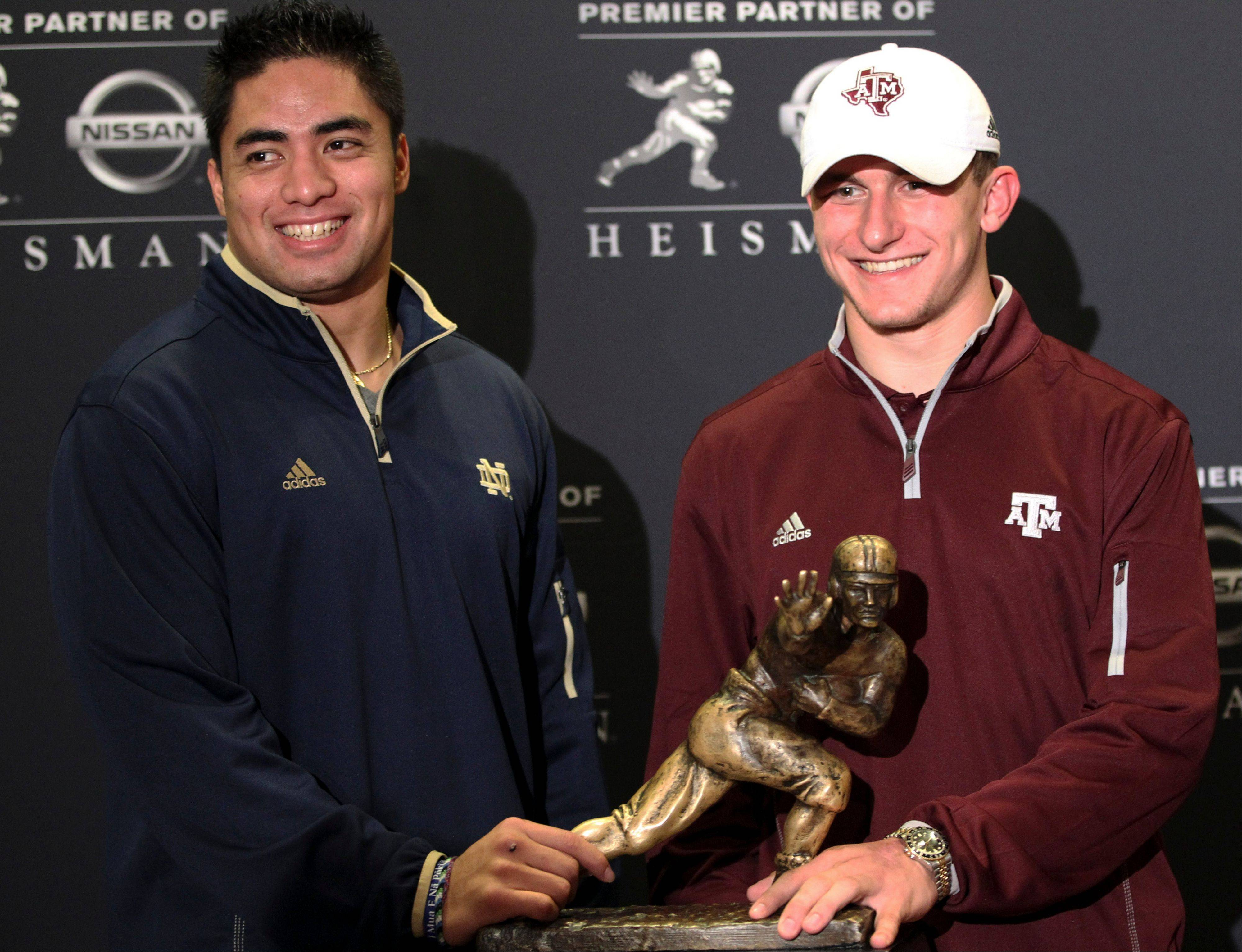 Notre Dame linebacker Manti Te'o and Texas A&M quarterback Johnny Manziel, two of the three Heisman Trophy finalists, pose with the Heisman Trophy Friday during a media availability in New York City.