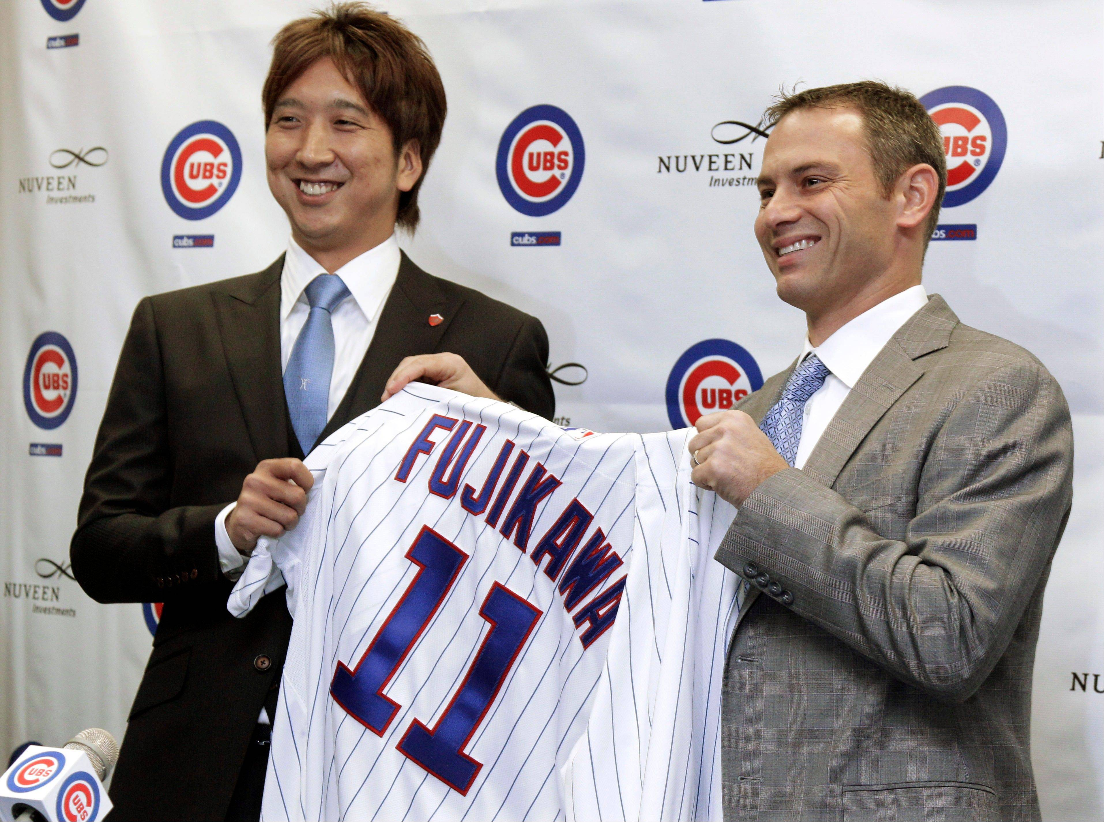 Cubs general manager Jed Hoyer presents a jersey to new pitcher Kyuji Fujikawa of Japan on Friday at Wrigley Field. Hoyer insists Carlos Marmol is the team's closer and says Fujikawa is an important addition to the team's bullpen.