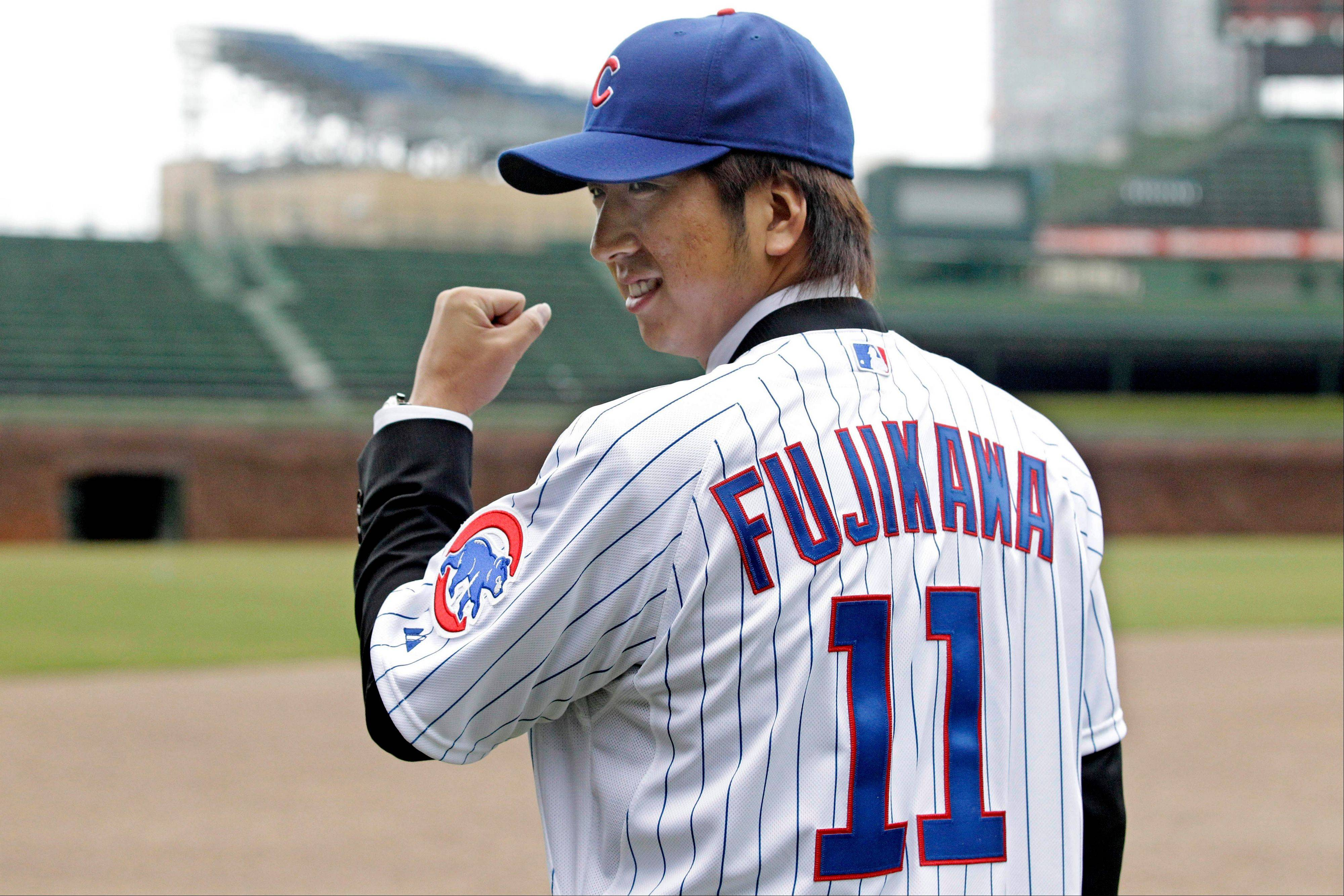 Kyuji Fujikawa, who was a closer in Japanese baseball for the Hanshin Tigers, poses for pictures at Wrigley Field after being introduced to the media Friday.