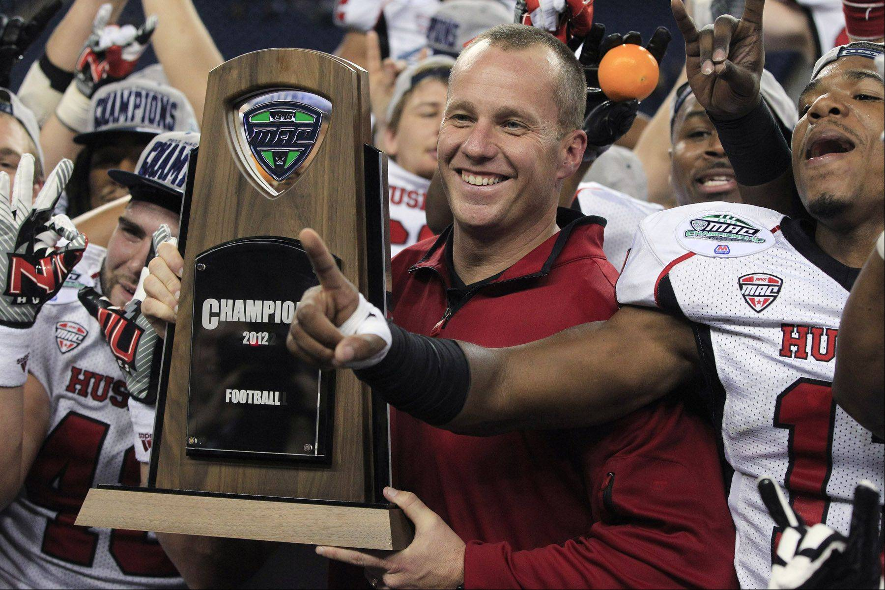 NIU coach Dave Doeren displays the Mid-American Conference championship trophy after his the Huskies beat Kent State 44-37 in double overtime Friday in Detroit. Less than 24 hours later, Doeren departed NIU to coach North Carolina State, a scenario Mike Spellman is having a hard time digesting.