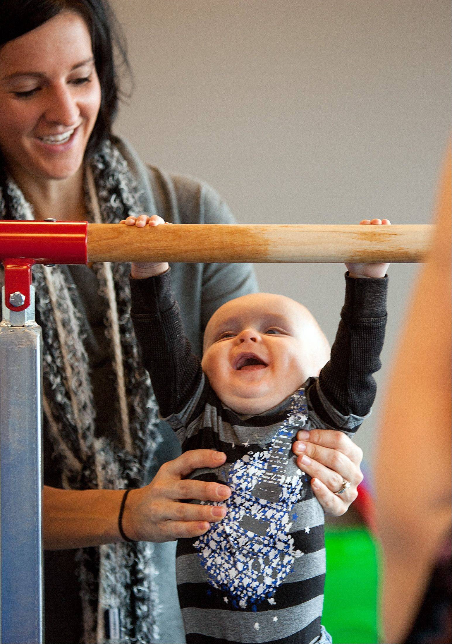 Bridgett Atwell of Mokena helps her 7-month-old son, Landon, hold onto the uneven bars Saturday in the gymnastics area of the Naperville Park District�s new 95th Street Center. The center hosted a grand opening Saturday morning for residents to explore its gymnastics, dance and culinary facilities.