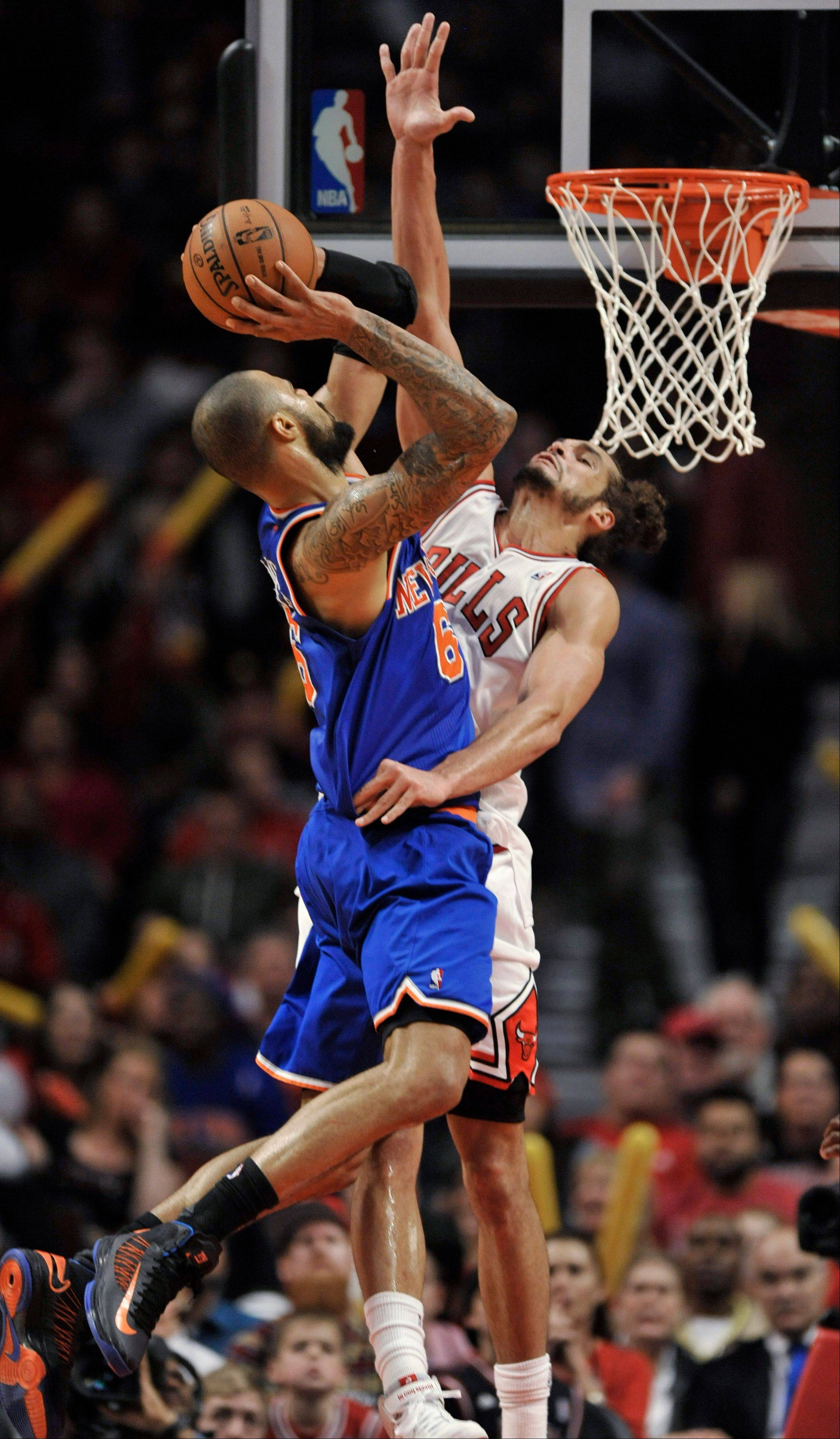 The Bulls' Joakim Noah goes up for the block and fouls the Knicks' Tyson Chandler on Saturday night.