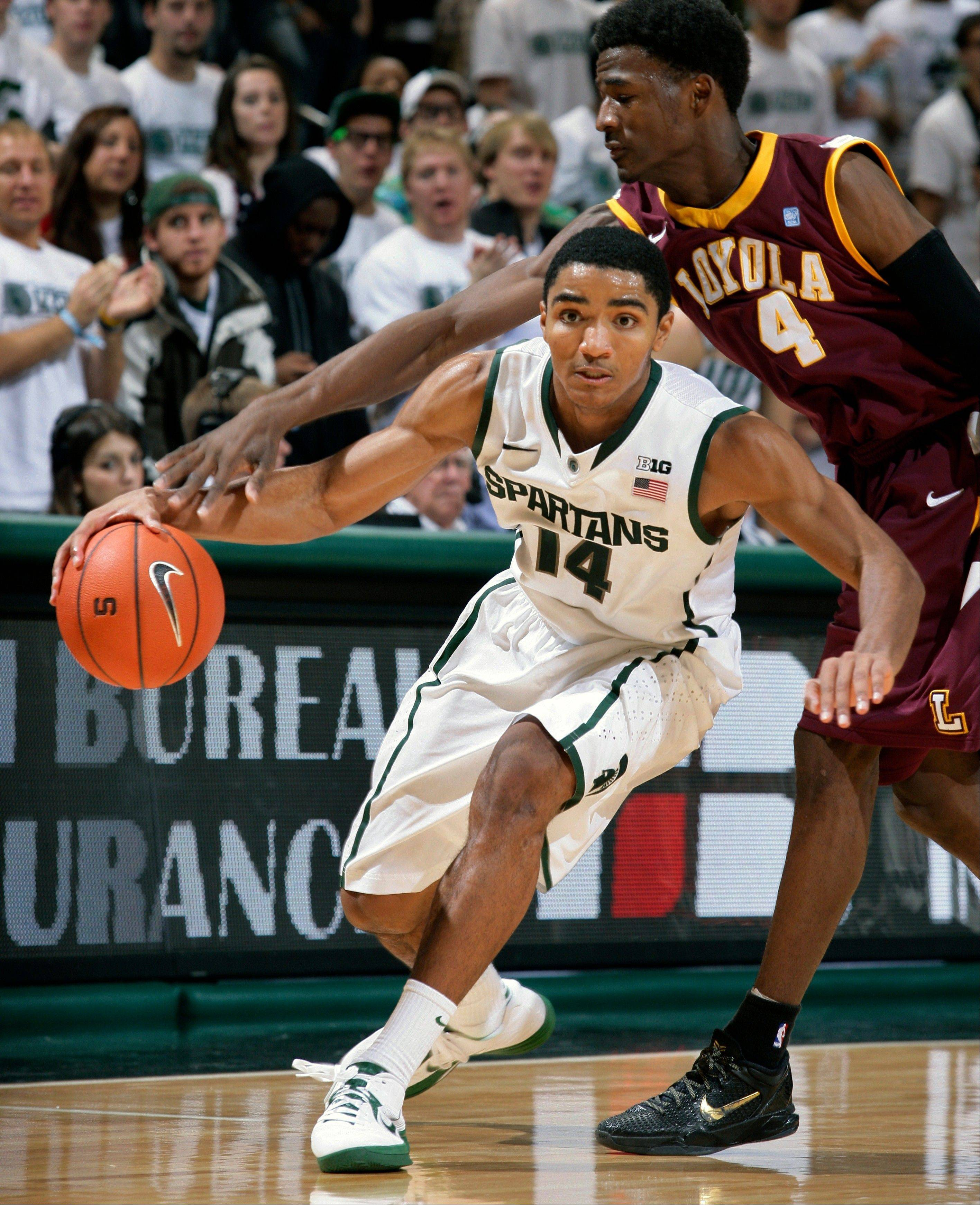 Michigan State�s Gary Harris (14) drives against Loyola�s Devon Turk during the second half Saturday in East Lansing, Mich. Harris led Michigan State with 20 points in a 73-61 win.