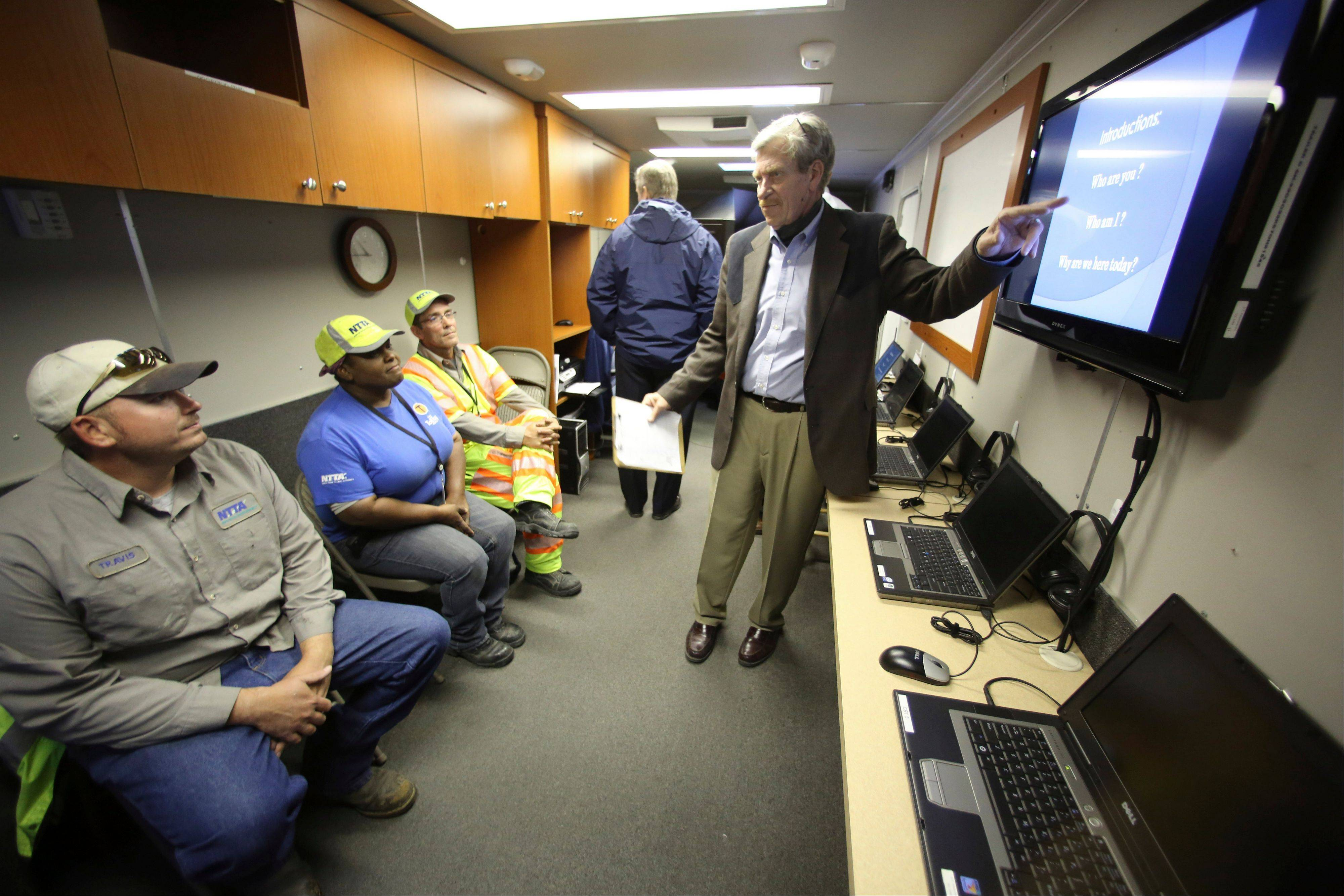 Instructor J. Stephens, right, talks to drivers, from left, Travis Roebuck, Regina Hall and Terence Mundt, before a snowplow simulator during a North Texas Tollway Authority training class in Plano, Texas.