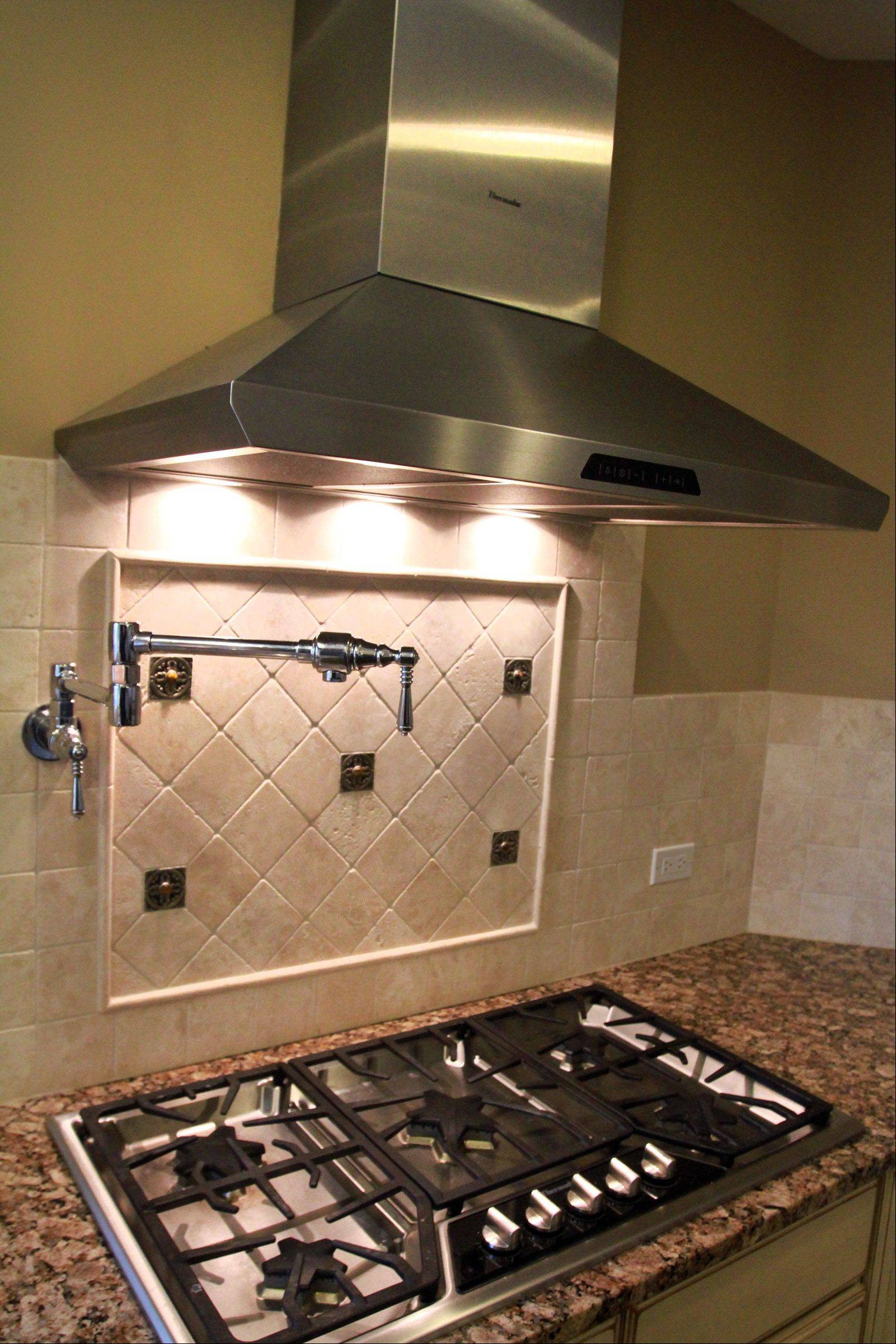 The Fretzin family kitchen includes a Thermador professional oven and range with a pot-filler faucet over the stove.