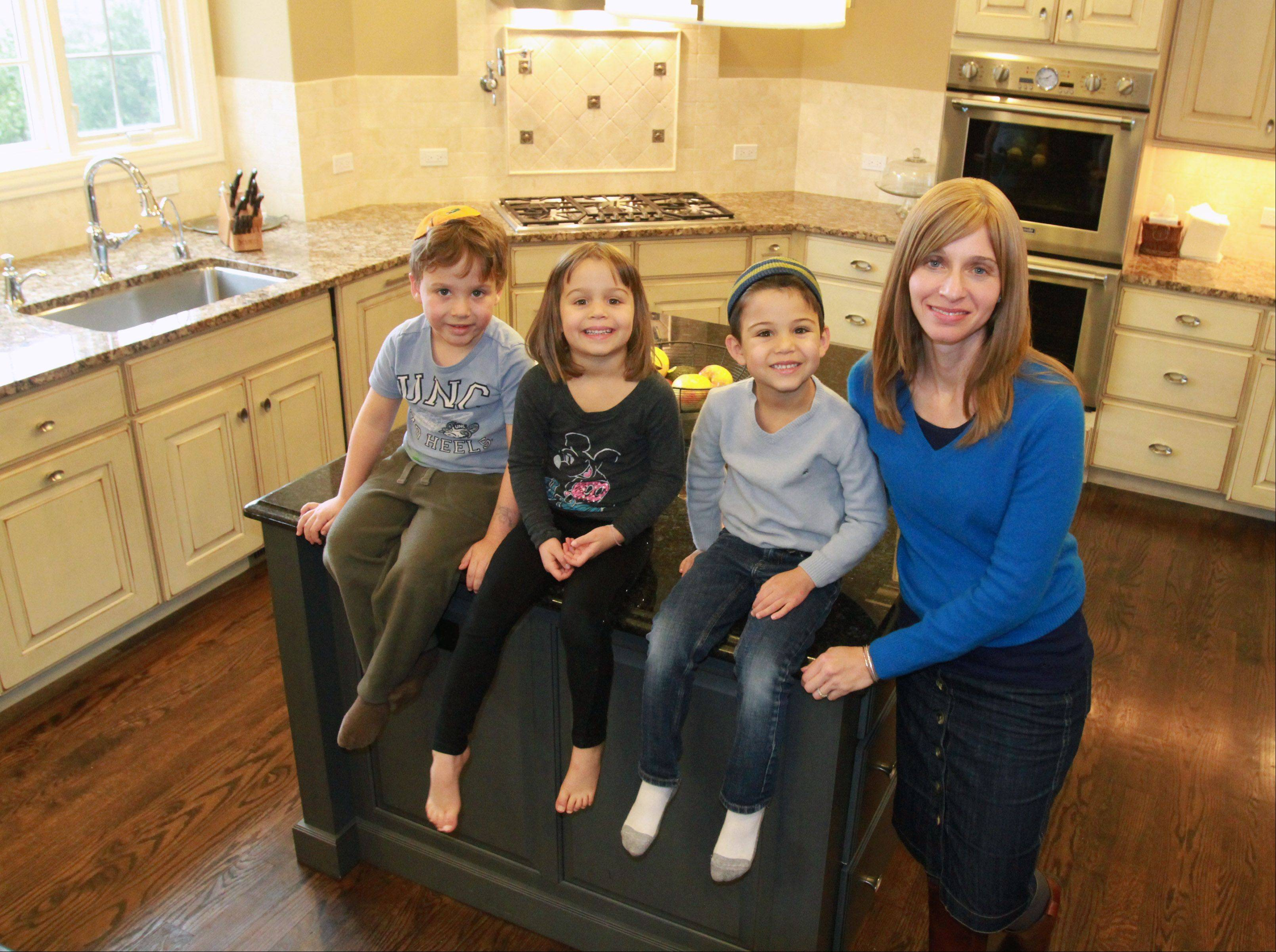 Robbie Fretzin enjoys her new ktichen with her children Estar, center, and Eli, right, with their friend, Judah Will, far left, all age 5, at her home in Skokie.