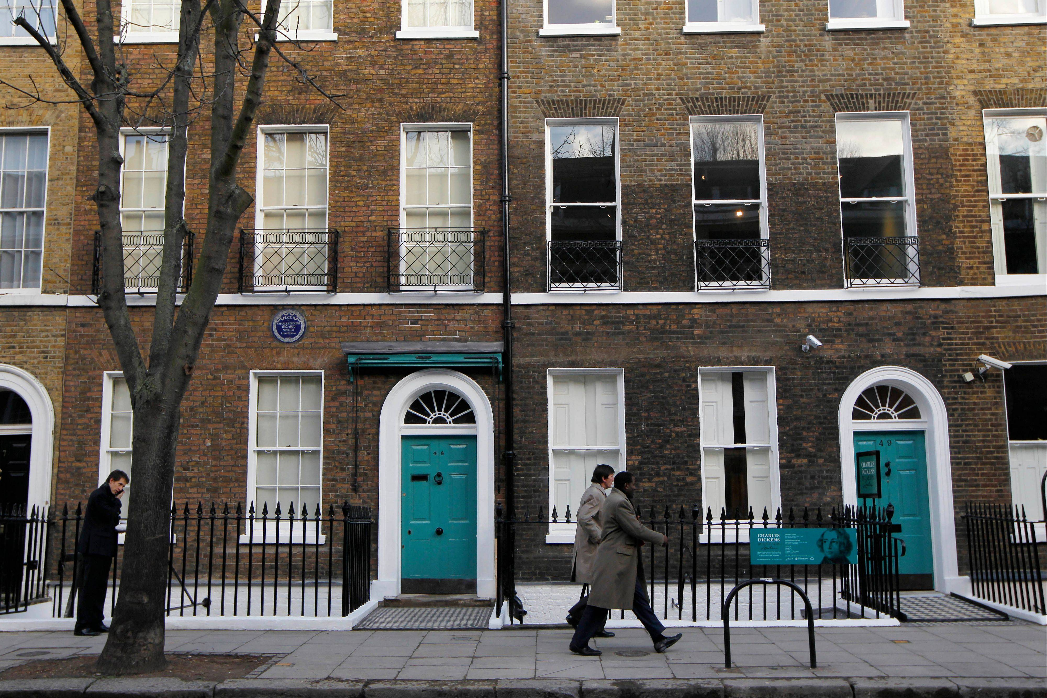 People walk past Charles Dickens' home, left, part of the Charles Dickens Museum in London. For years, the four-story brick row house where the author lived with his young family was a neglected museum.