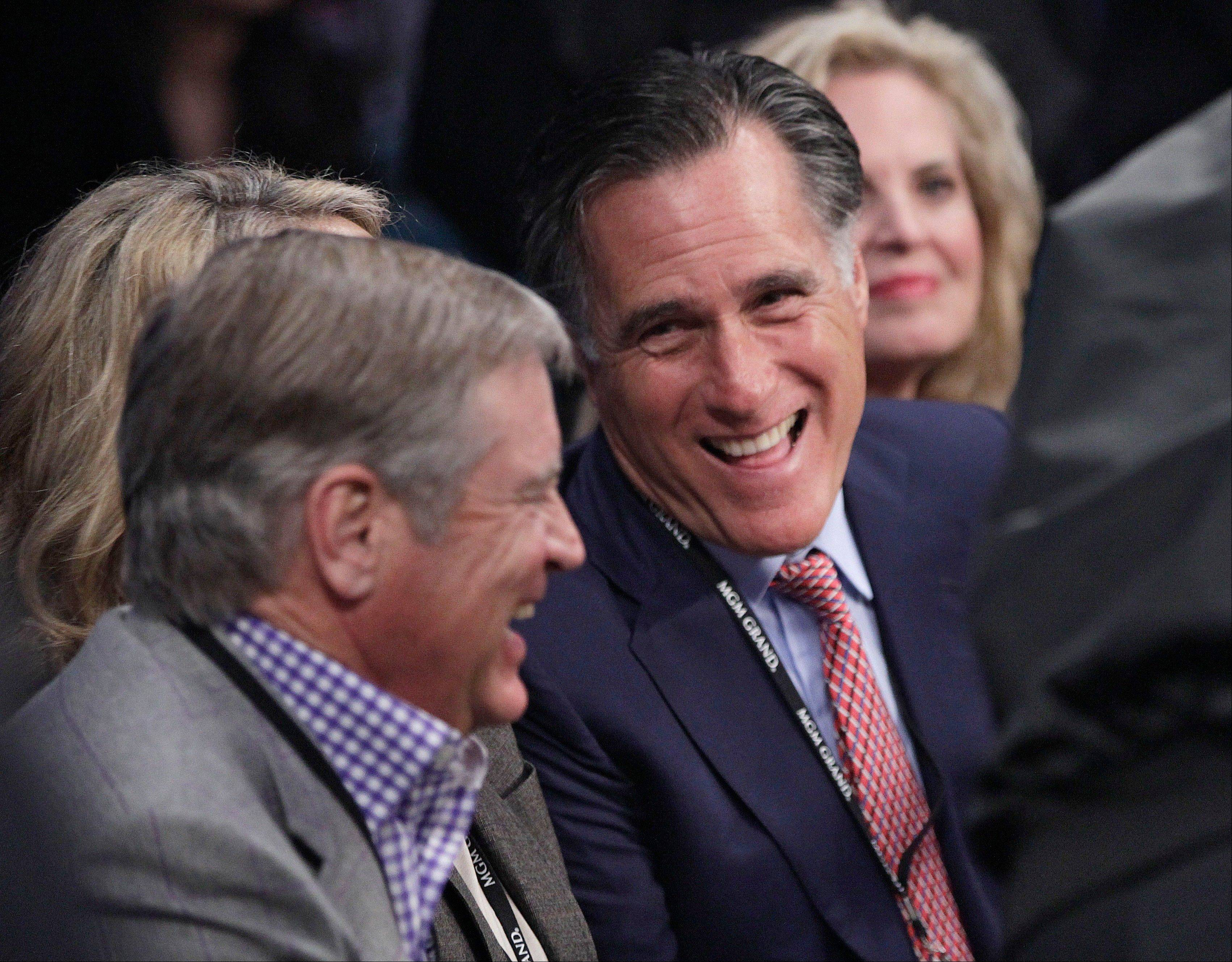 Former Republican presidential candidate Mitt Romney, center, joined by wife Ann, right, talks with an unidentified spectator at ringside prior to a welterweight title fight between Juan Manuel Marquez and Manny Pacquiao in Las Vegas.