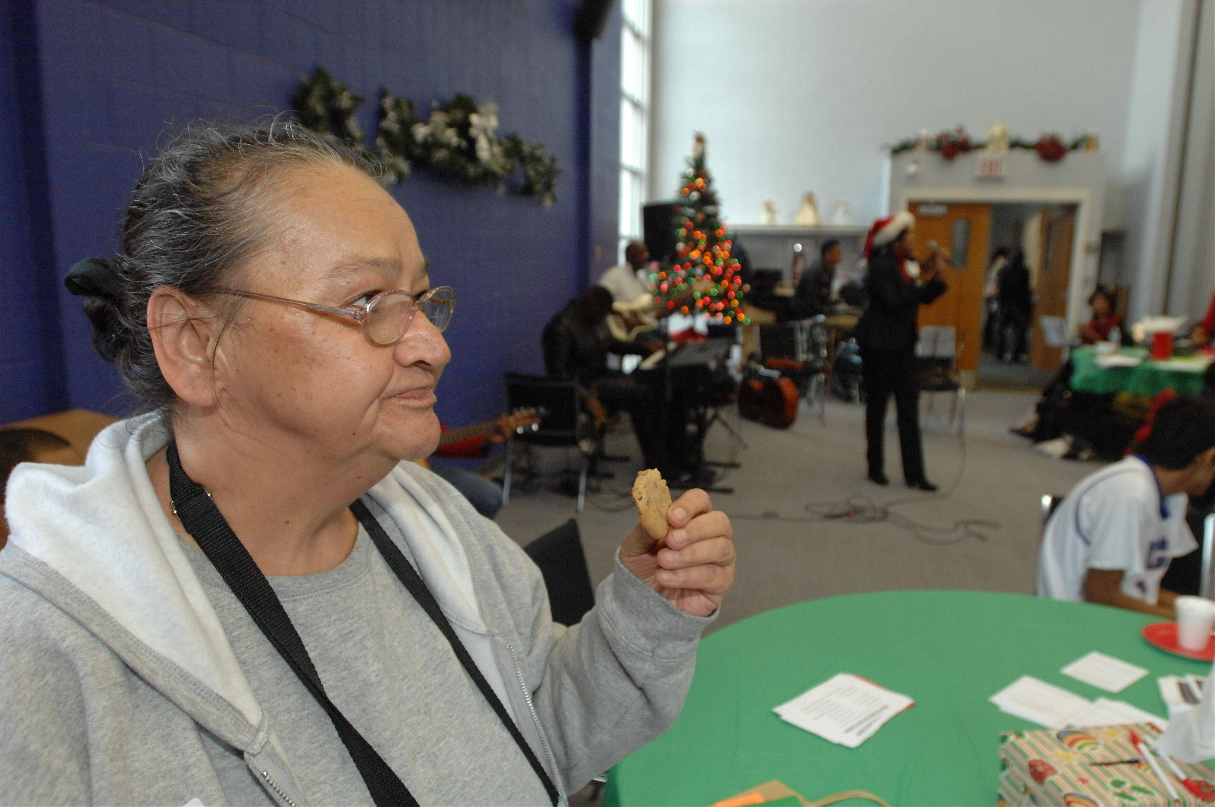 Carol Olson of Carol Stream enjoys a cookie while listening to holiday music Saturday during the Outreach Community Center's Christmas Store. About 440 families were able to choose two gifts for each child at a 75 percent discount during the 18th annual event.