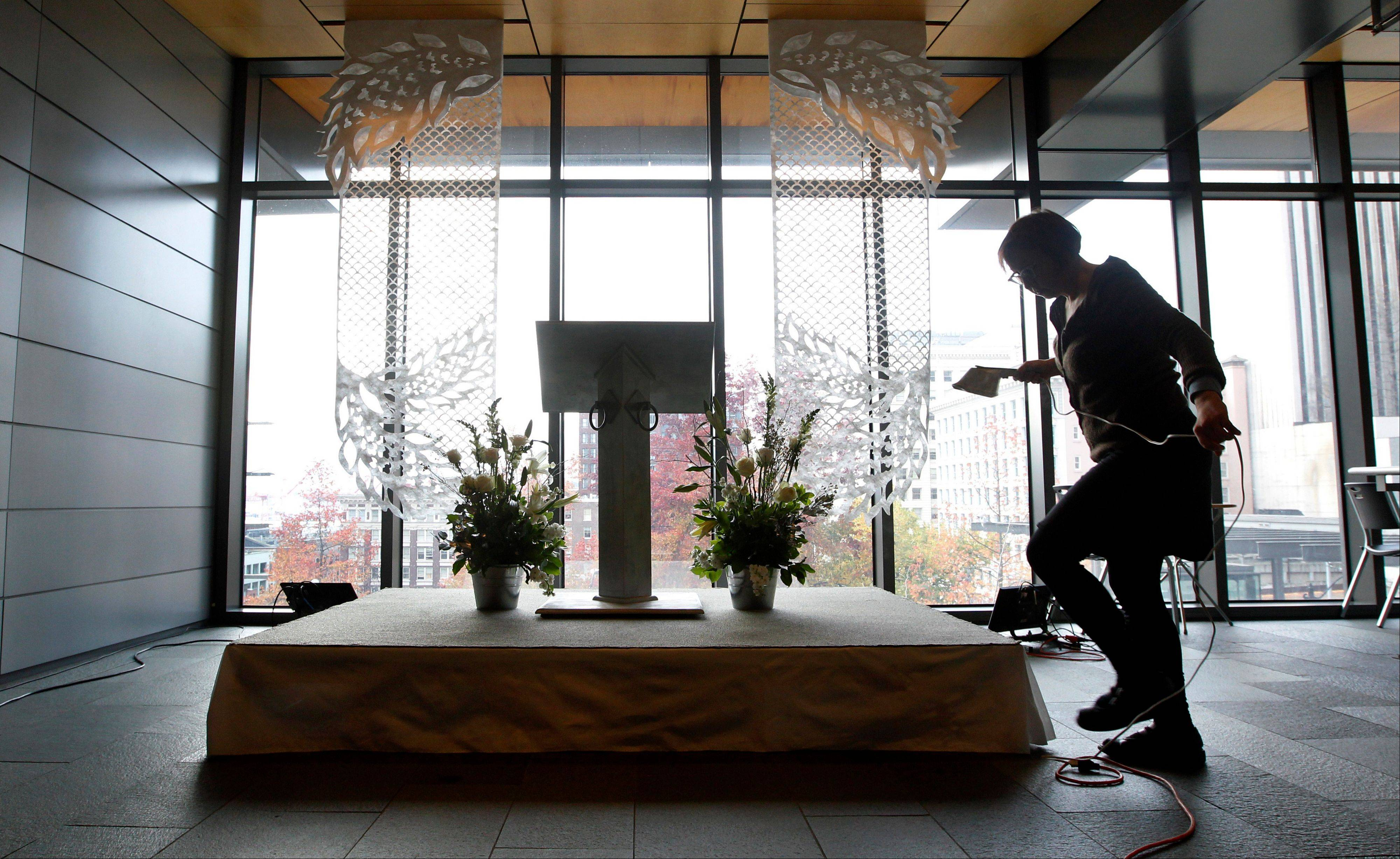Volunteer Jane Richlovsky puts finishing touches Saturday on one of five spots in Seattle City Hall where weddings will take place on Sunday.