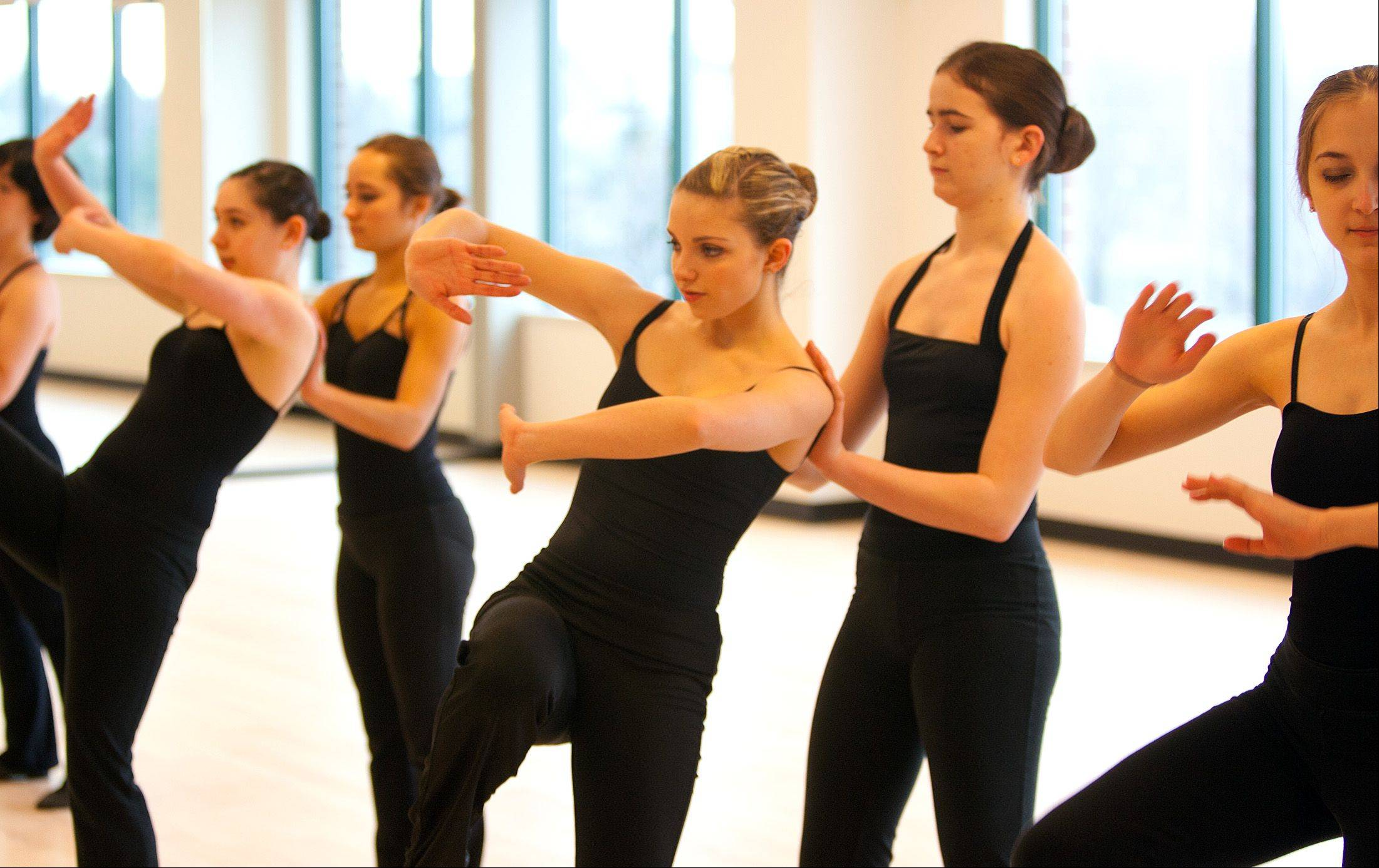 Benet Academy senior Lindsay Gloor, center, leads the �lan Dance Company in a performance Saturday as the Naperville Park District holds a grand opening at its new 95th Street Center.