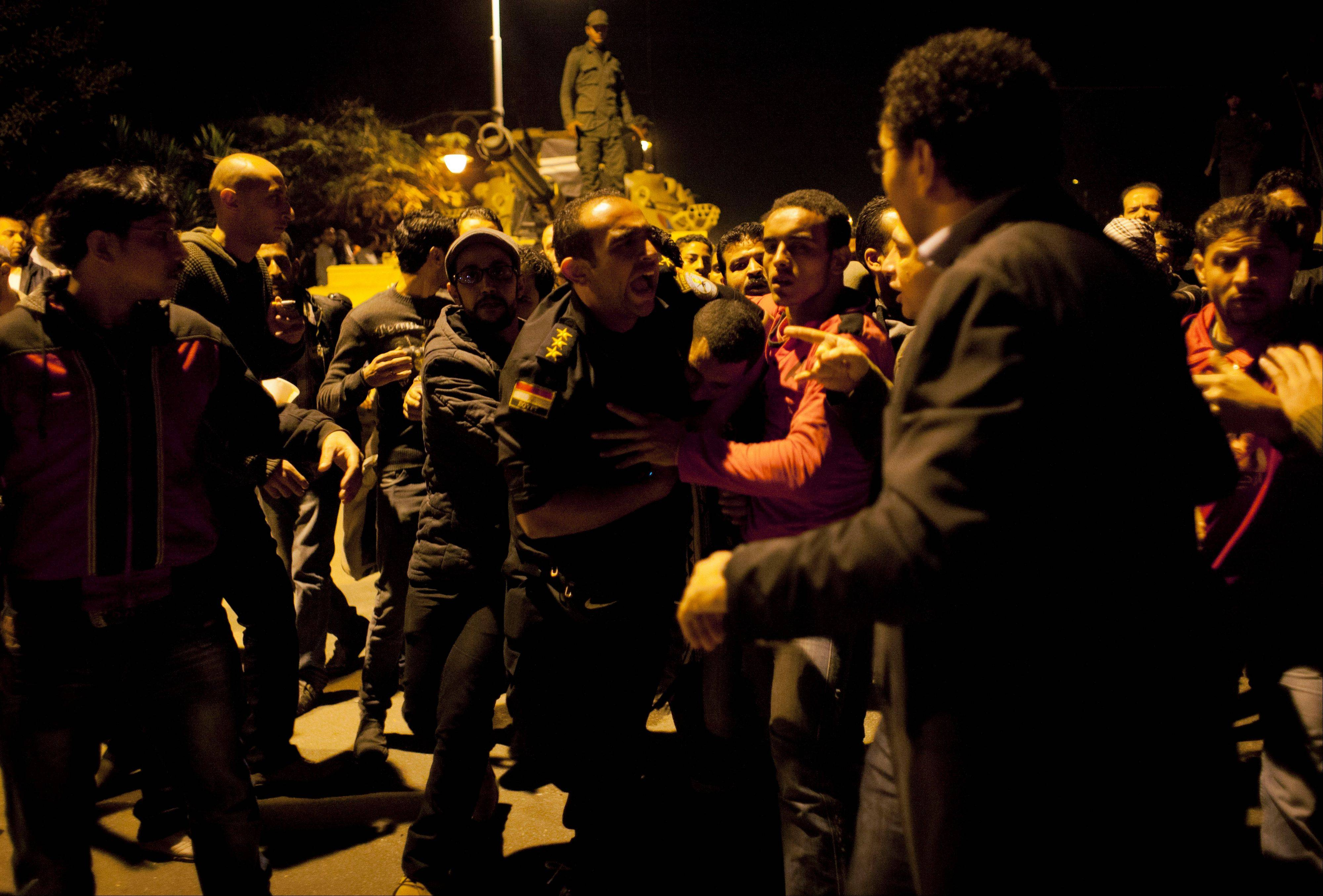 An Egyptian army officers detain and protect a man who was attacked by protesters accusing him of being an agent of the Muslim Brotherhood during protests Friday opposing Egyptian President Mohammed Mosri, at the walls of the presidential palace.