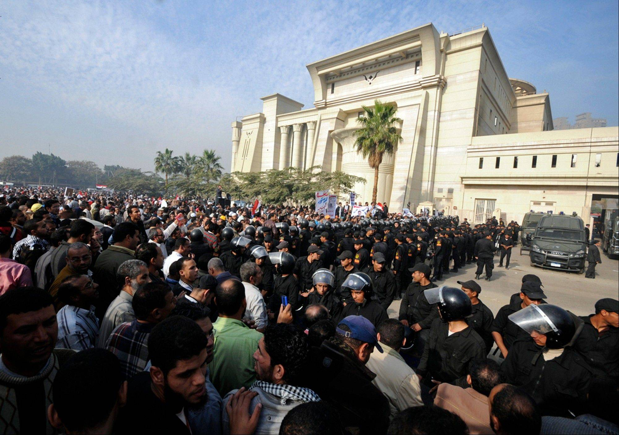 Associated Press/Sunday, Dec. 2Riot police form a cordon as several thousand supporters of Islamist President Mohammed Morsi surround the Supreme Constitutional Court on Sunday to prevent the judges from entering and ruling on the legitimacy of the nation's Islamist-dominated constituent assembly.