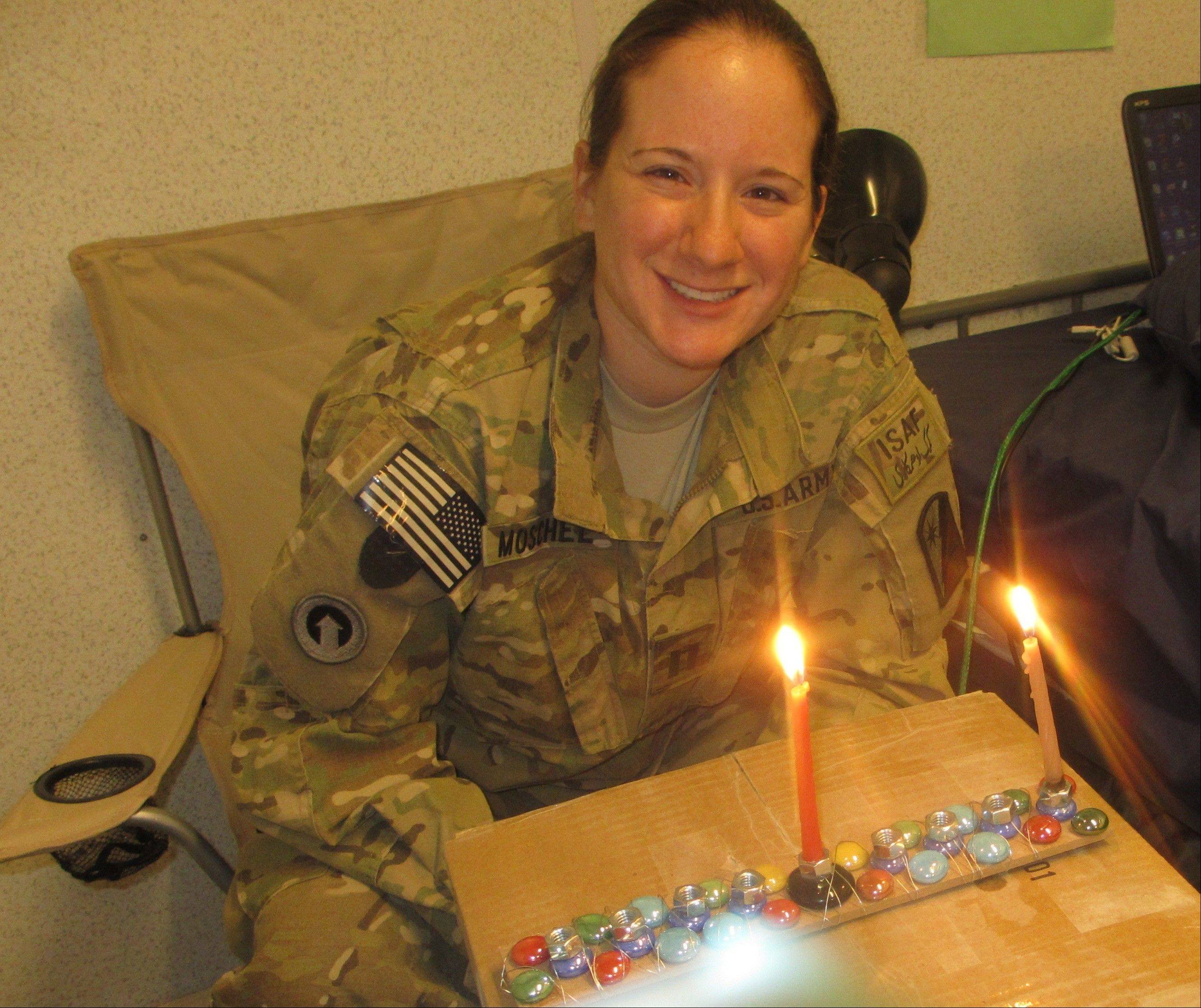 Captain Becky Moschel lights a menorah made by students at Anshe Tikvah on the first night of Hanukkah while serving in Afghanistan.