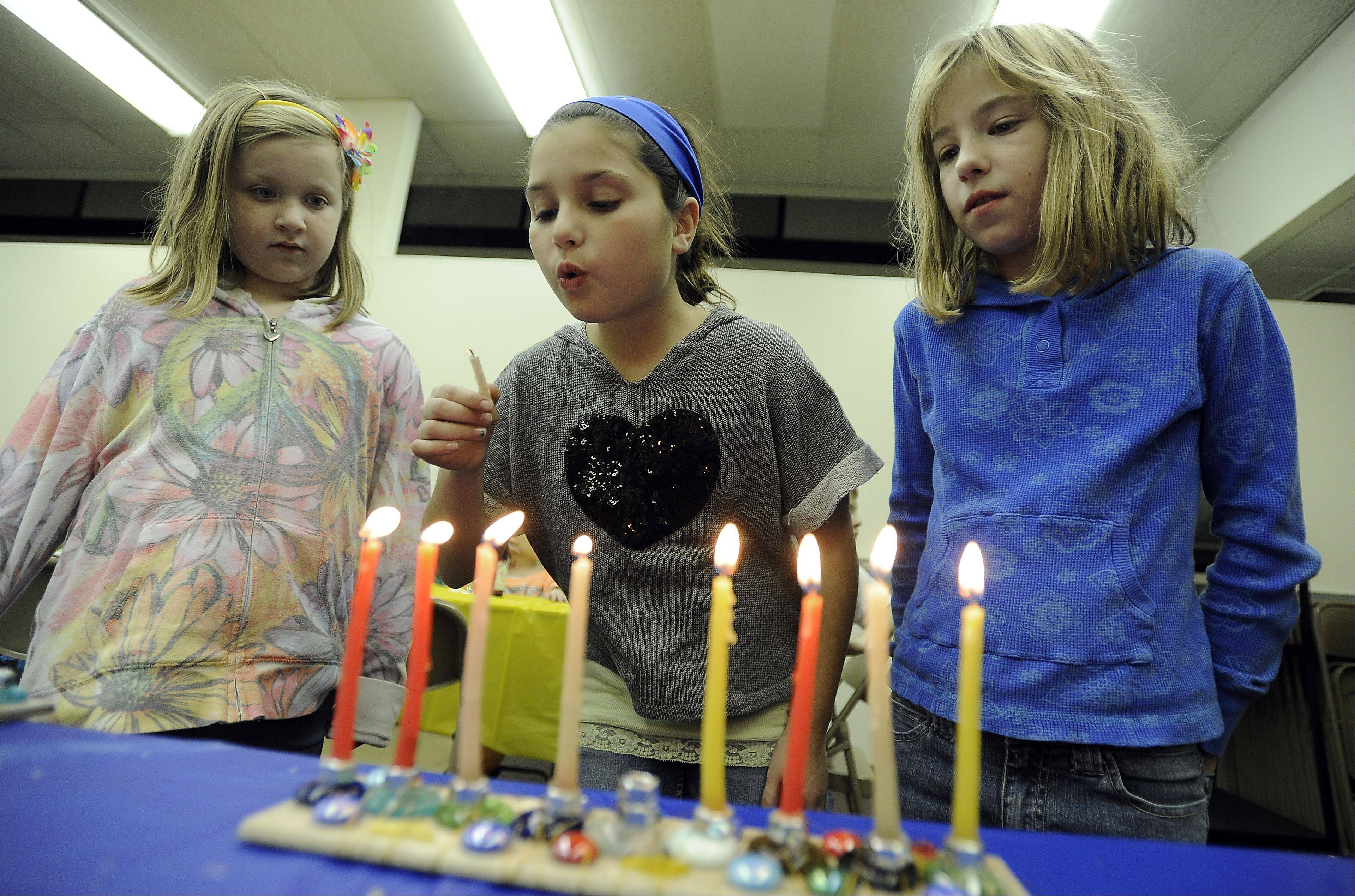 Camryn Litka, 8, of Wauconda, Sophie Veytsman, 9, of Arlington Heights and Sidney Zuber, 11, of Buffalo Grove light the Hanukkah menorah during religious school at Anshe Tikvah.