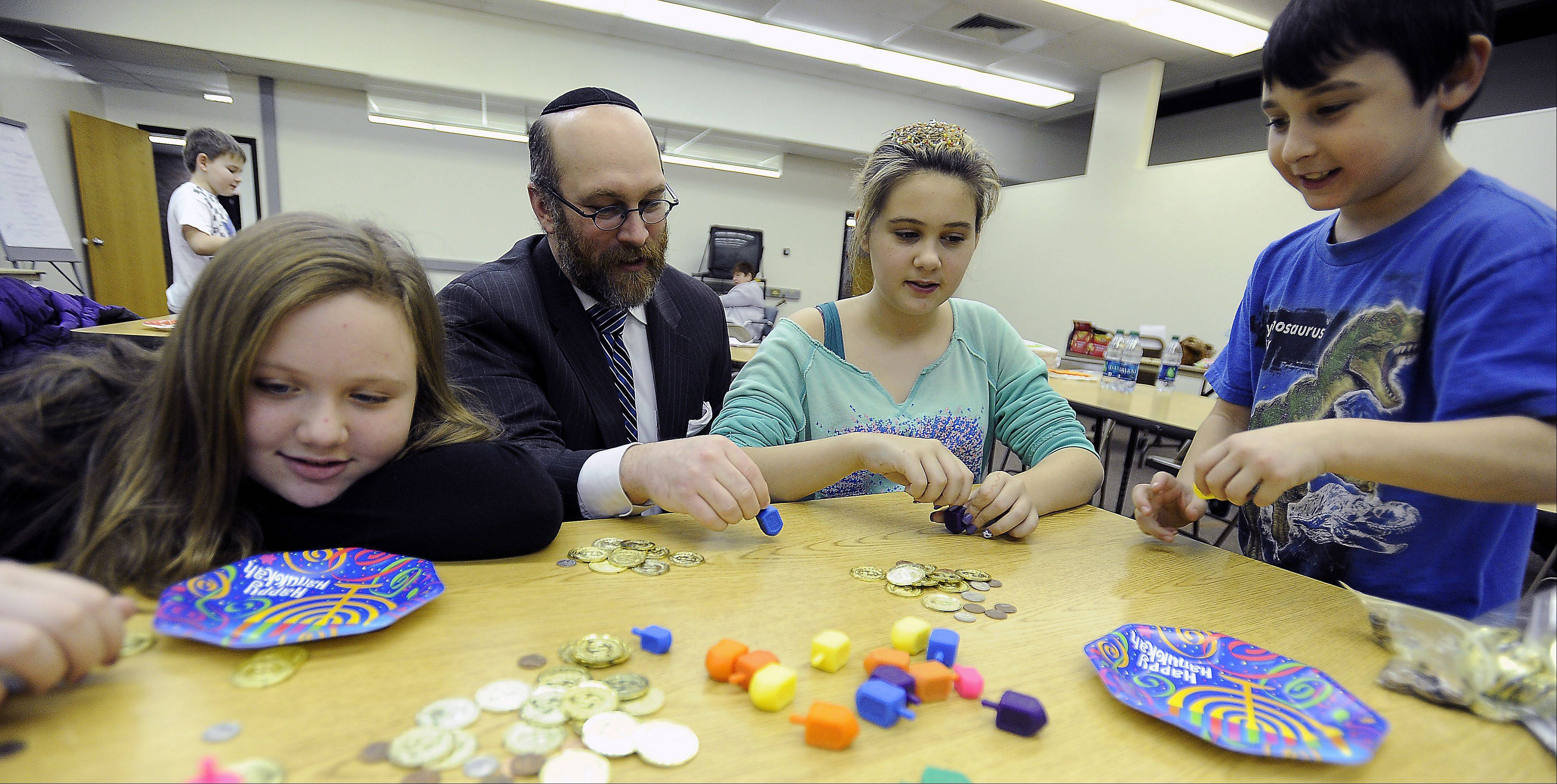 Rabbi Rob Jury plays a game of spin the dreidel with Sydney Litka of Wauconda, Sydney Hall of Palatine and Chase Rosen of Wheeling during religious school at Anshe Tikvah.