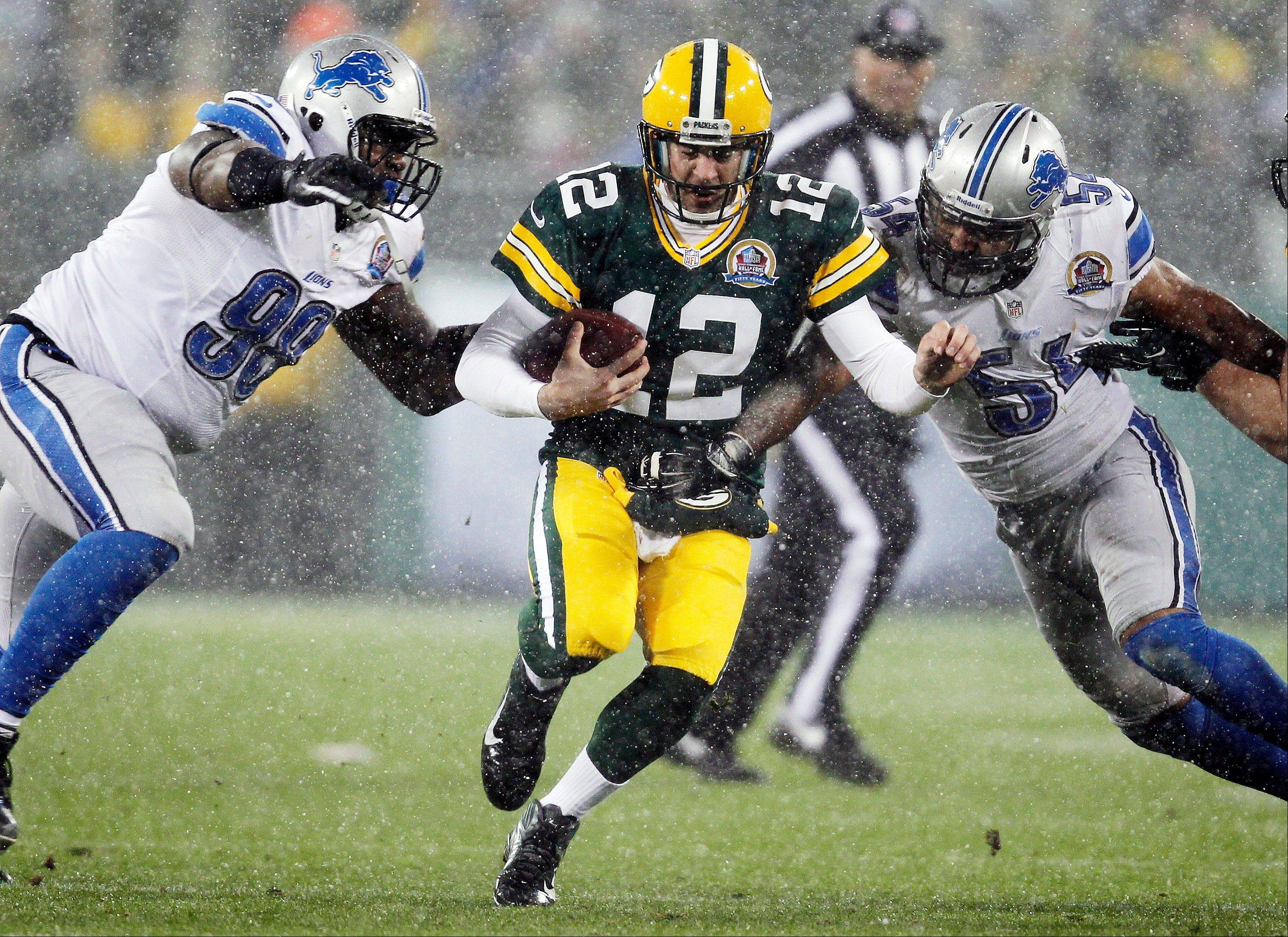Green Bay Packers quarterback Aaron Rodgers (12) runs for yardage between Detroit Lions' Nick Fairley (98) and DeAndre Levy (54) during an NFL football game Sunday in Green Bay, Wis. NBC broadcast the game nationally.