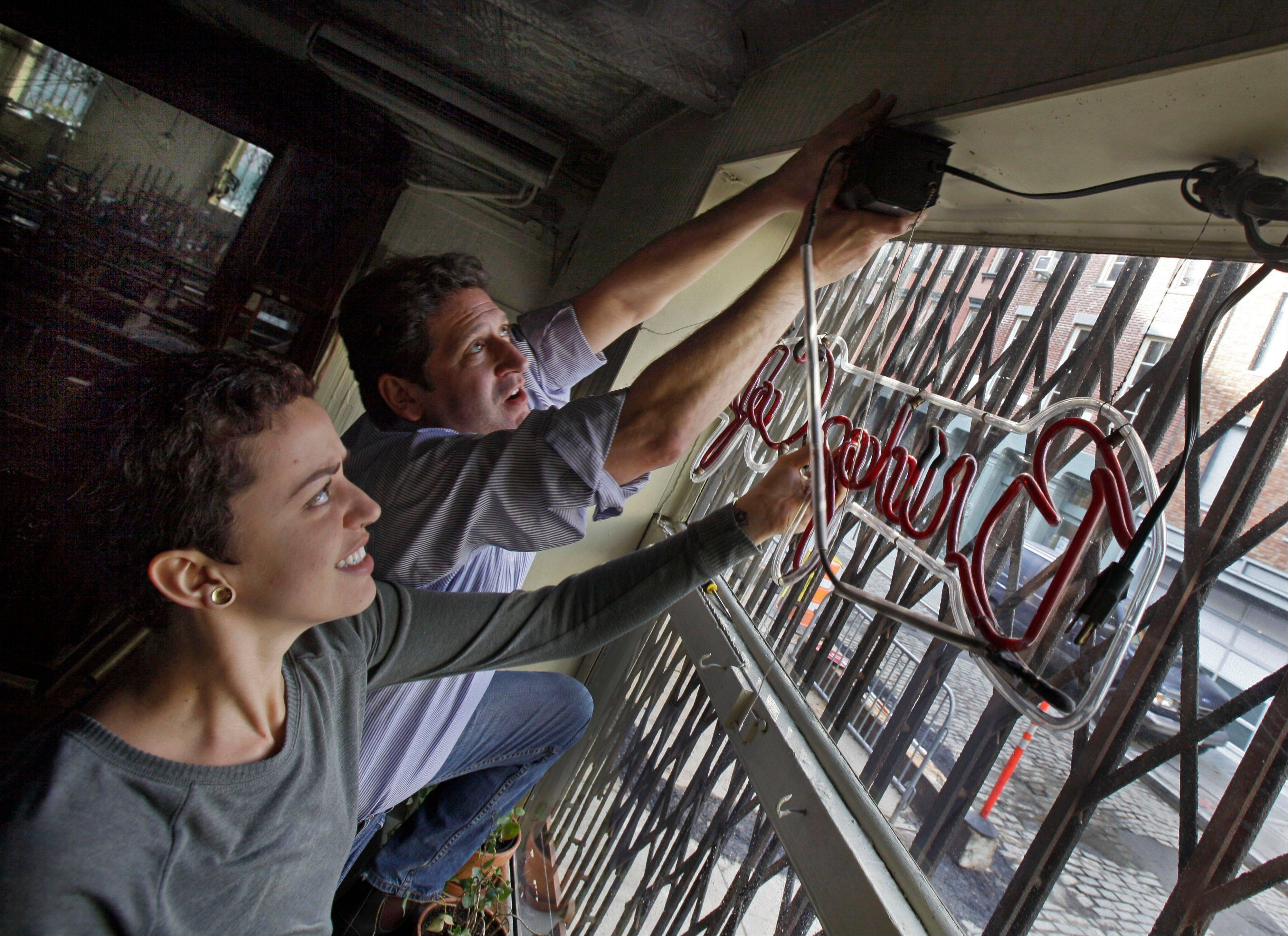 Bridge Cafe General Manager Ludmila Silva and proprietor Adam Weprin take down the restaurant's neon sign Tuesday at the restaurant in New York's South Street Seaport. Like many small business owners in the Northeast whose stores, restaurants, factories and offices were devastated or destroyed by the Oct. 29 storm, Weprin is hoping that federal, state and local officials will quickly come up with grants to help him rebuild and survive.