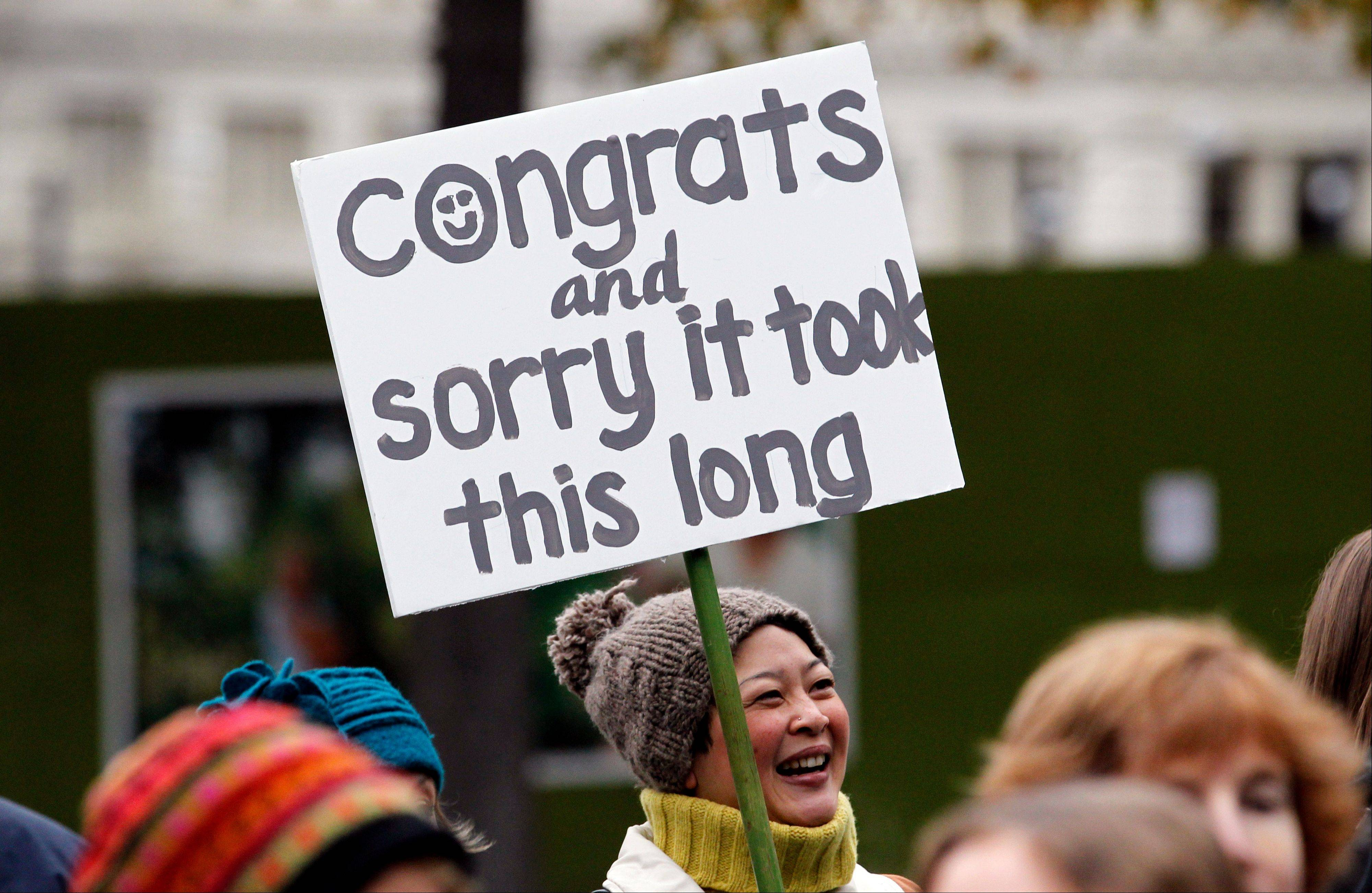 Cindy Ogasawara stands with other well-wishers greeting newly married couples as they depart Seattle City Hall Sunday. Washington state Gov. Chris Gregoire signed a voter-approved law legalizing gay marriage Wednesday, and weddings for gay and lesbian couples began Sunday.