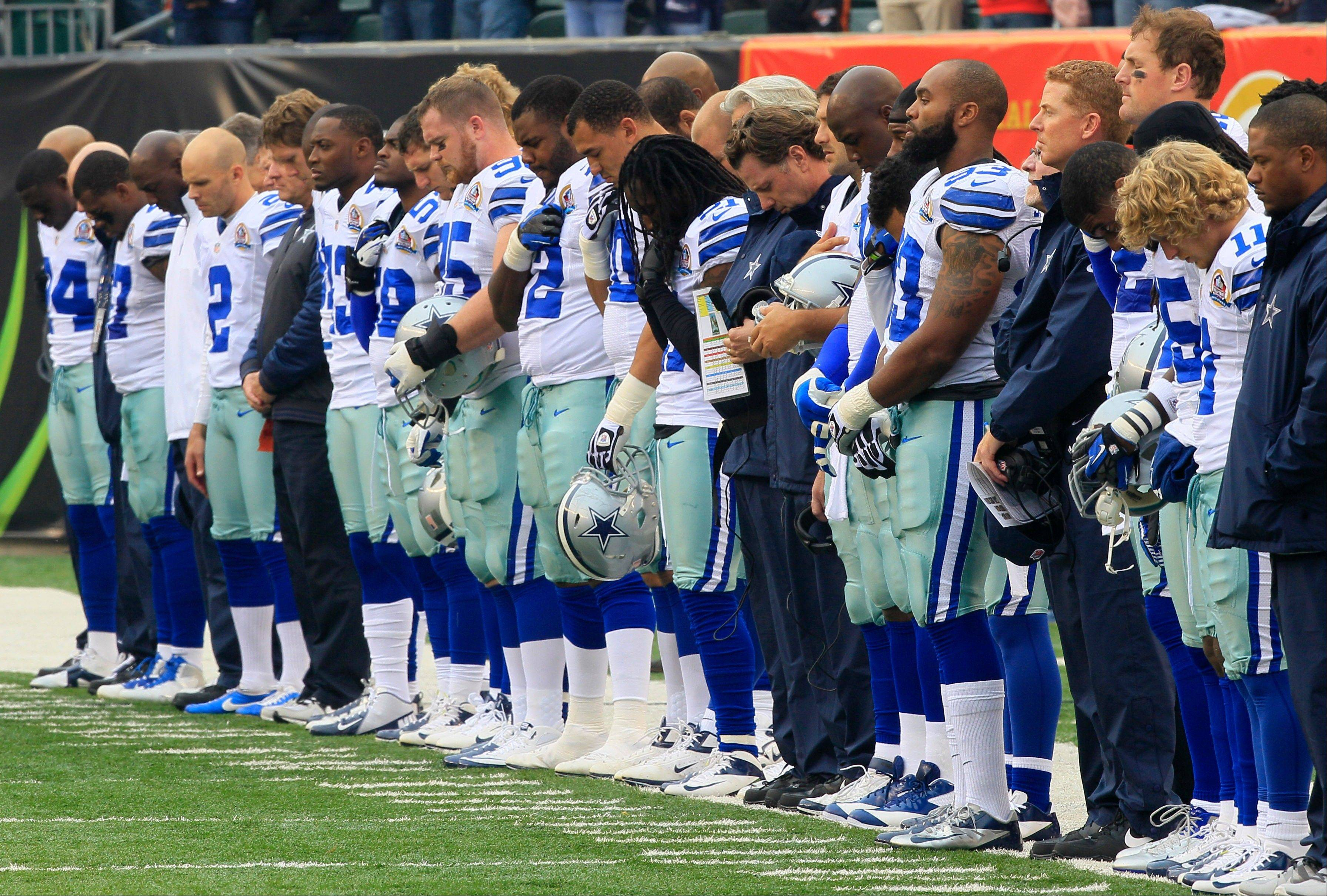 Dallas Cowboys players hang their heads during a moment of silence honoring teammate Jerry Brown who was killed in an automobile accident prior to an NFL football game against the Cincinnati Bengals, Sunday, Dec. 9, 2012, in Cincinnati.