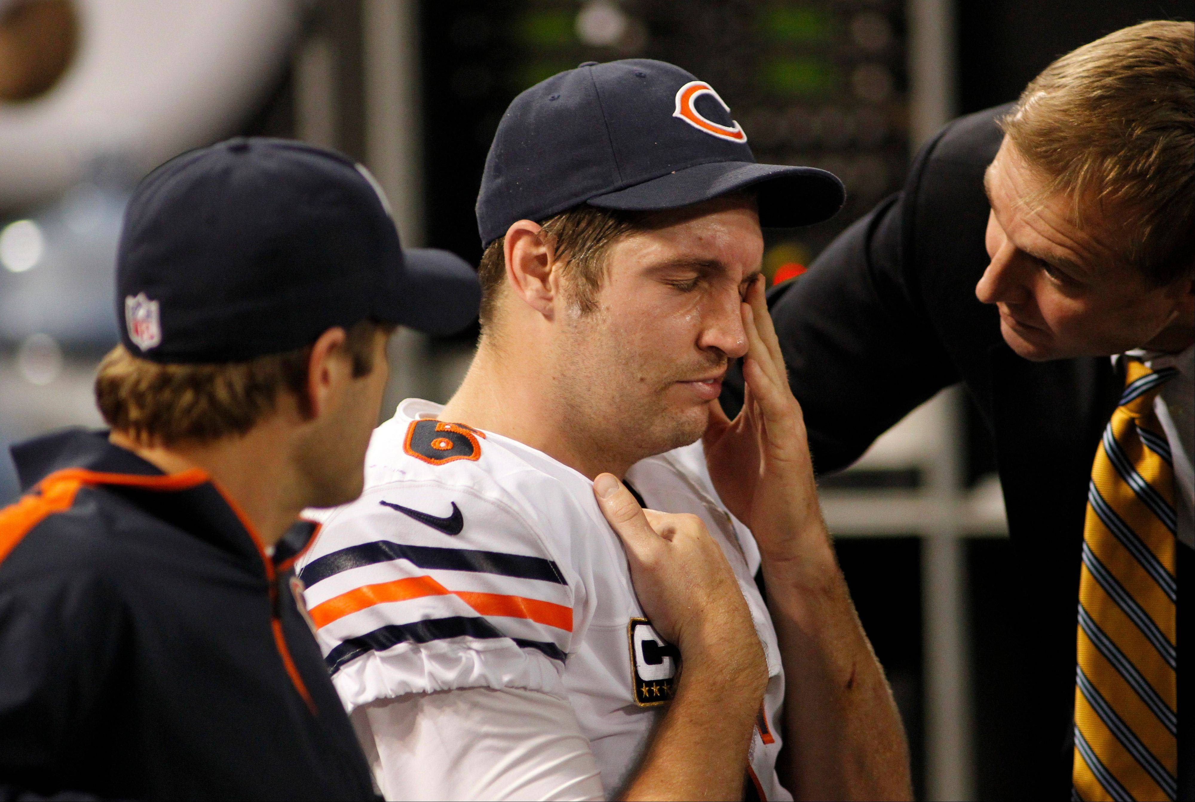 Bears quarterback Jay Cutler, center, watches the end of Sunday's game from the bench after taking a hit to the head in the Bears' loss to Minnesota.
