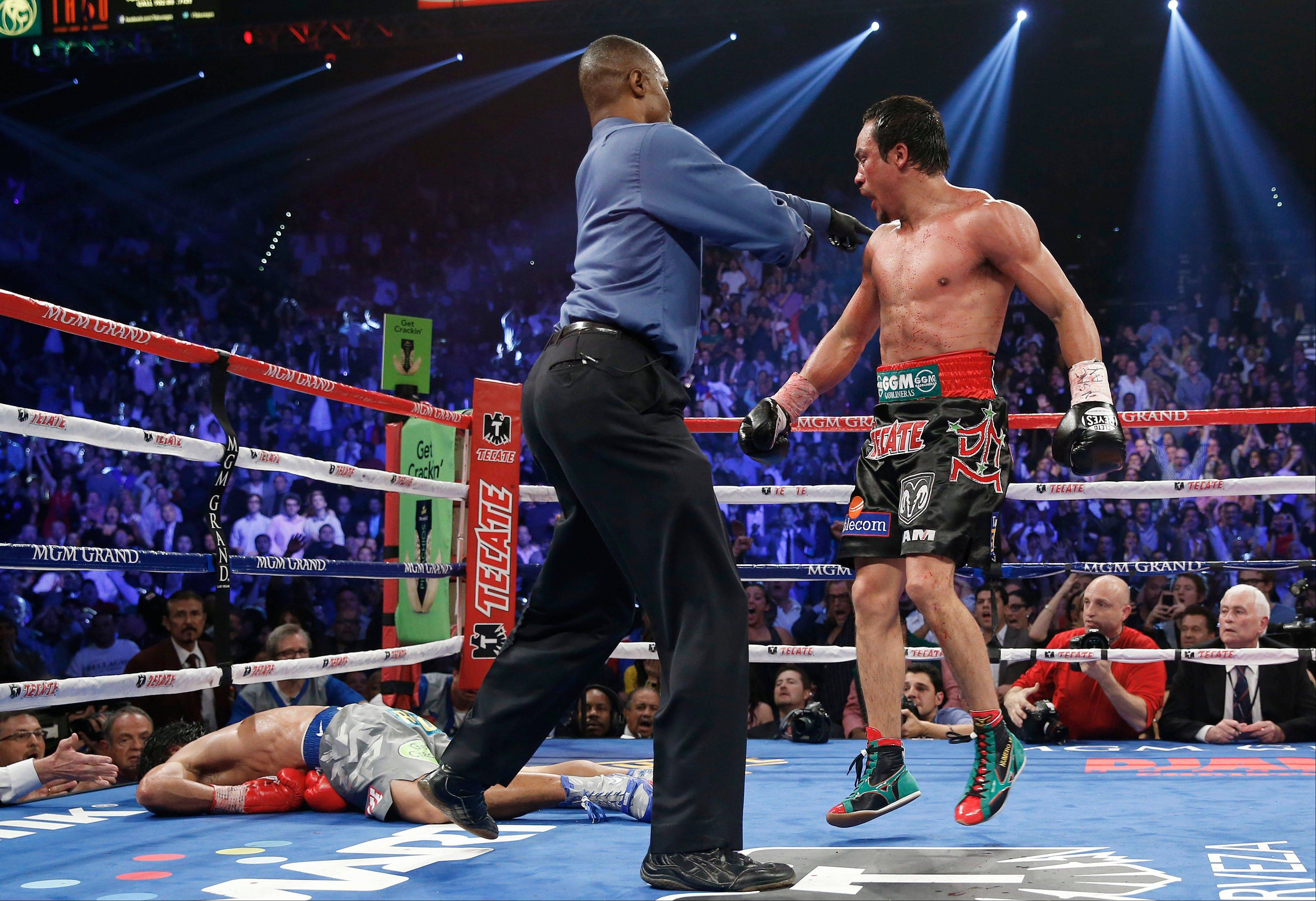 Referee Kenny Bayless, center, sends Juan Manuel Marquez, from Mexico, right, to his corner after he knocked out Manny Pacquiao, from the Philippines, left in the sixth round of their WBO world welterweight fight Saturday, Dec. 8, 2012, in Las Vegas. (AP Photo/Eric Jamison)