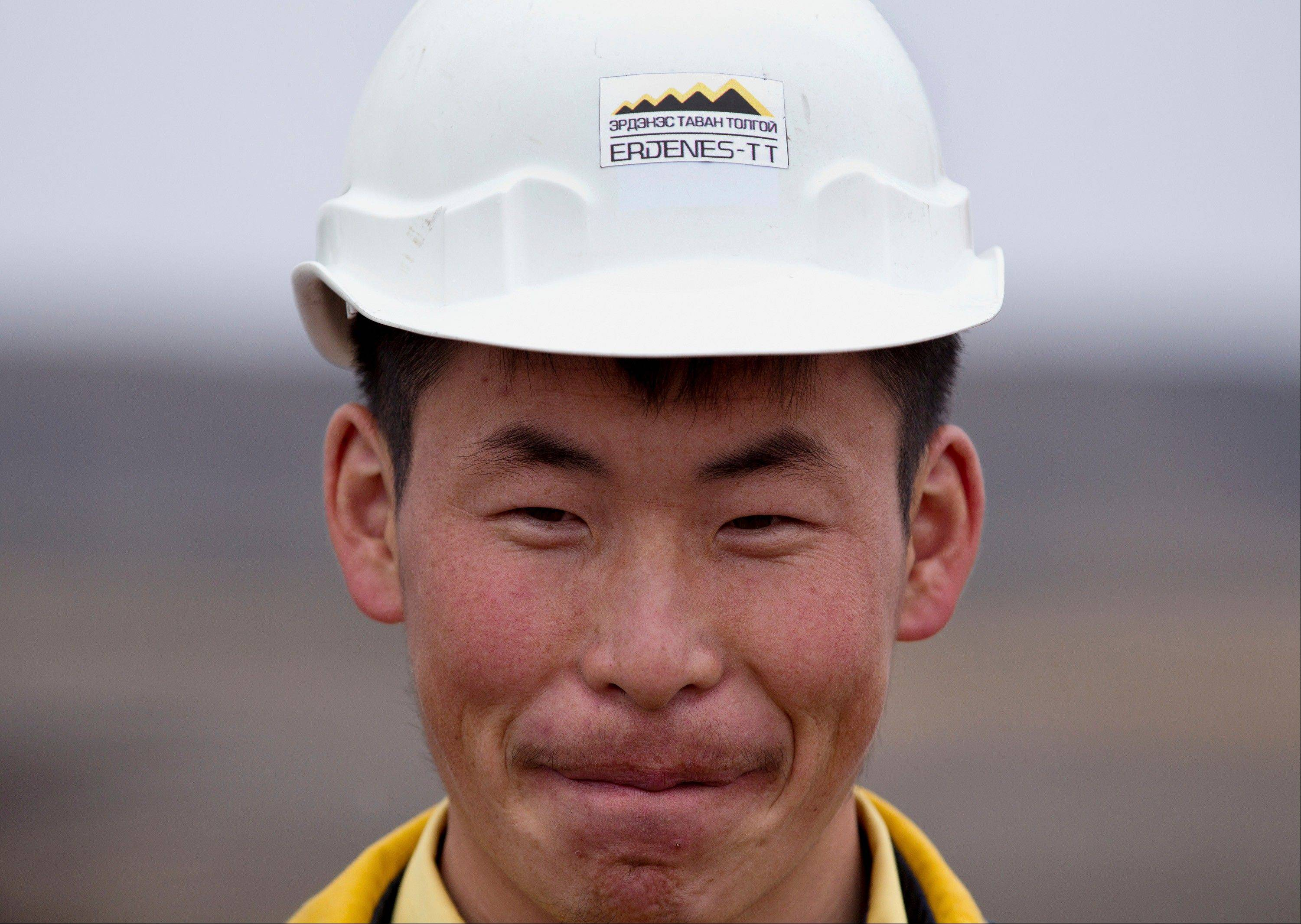 A Mongolian miner smiles while working at Erdenes Tavan Tolgoi, a coal mining company in Tavan Tolgoi, southern Mongolia. Chinese demand for copper and especially coal has propelled the Mongolian economy to one of the world's fastest growing, making some wealthy and driving down poverty in a still poor country, and China wants a larger share of the resources.