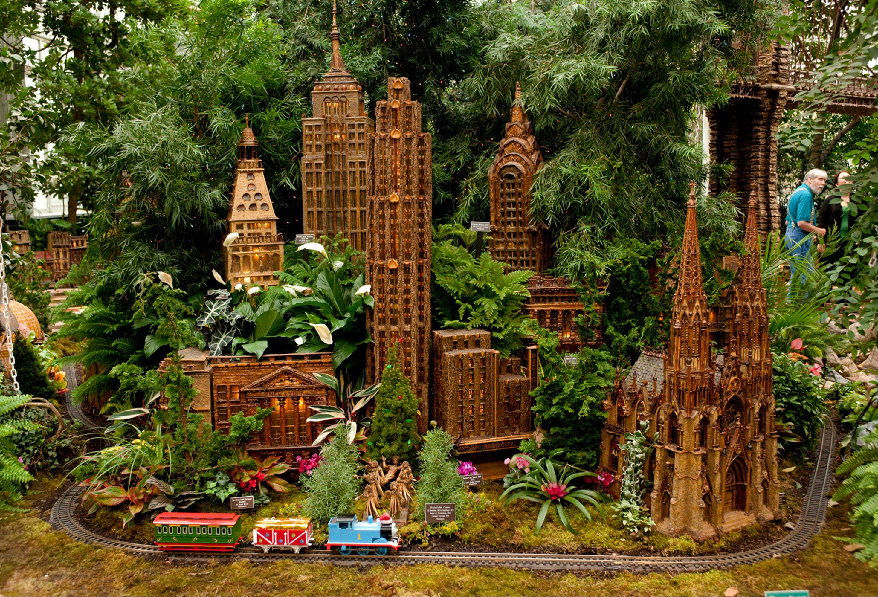 At the annual holiday train show at the New York Botanical Garden, model trains wind past 140 buildings depicting New York City, including landmarks like the original Yankee Stadium, St. Patrick's Cathedral and the Brooklyn Bridge.
