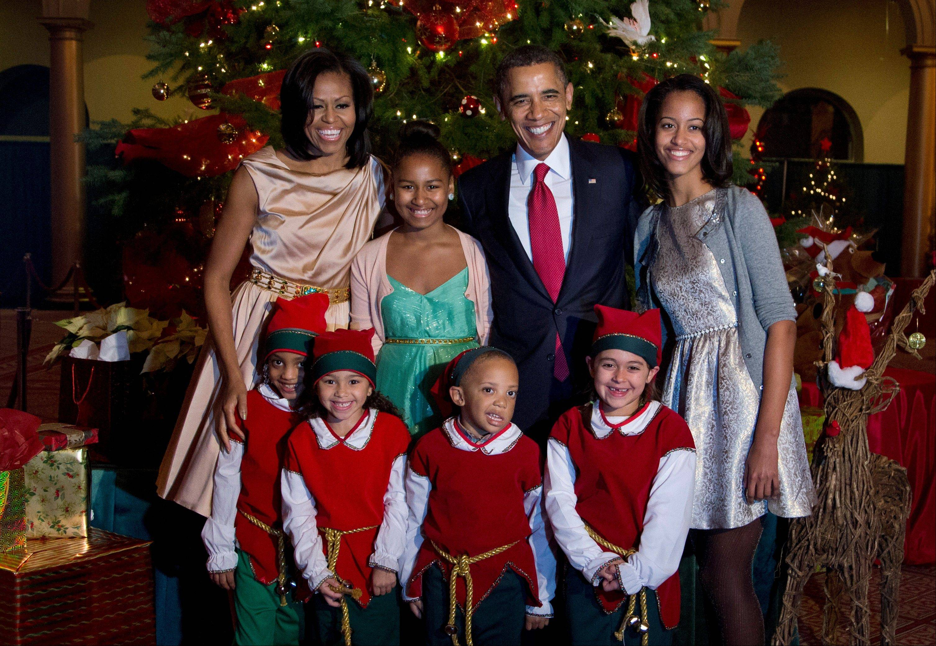 The first family, from left, first lady Michelle Obama, Sasha Obama, President Barack Obama and Malia Obama, pose with children dressed like elves at the National Building Museum in Washington, Sunday.