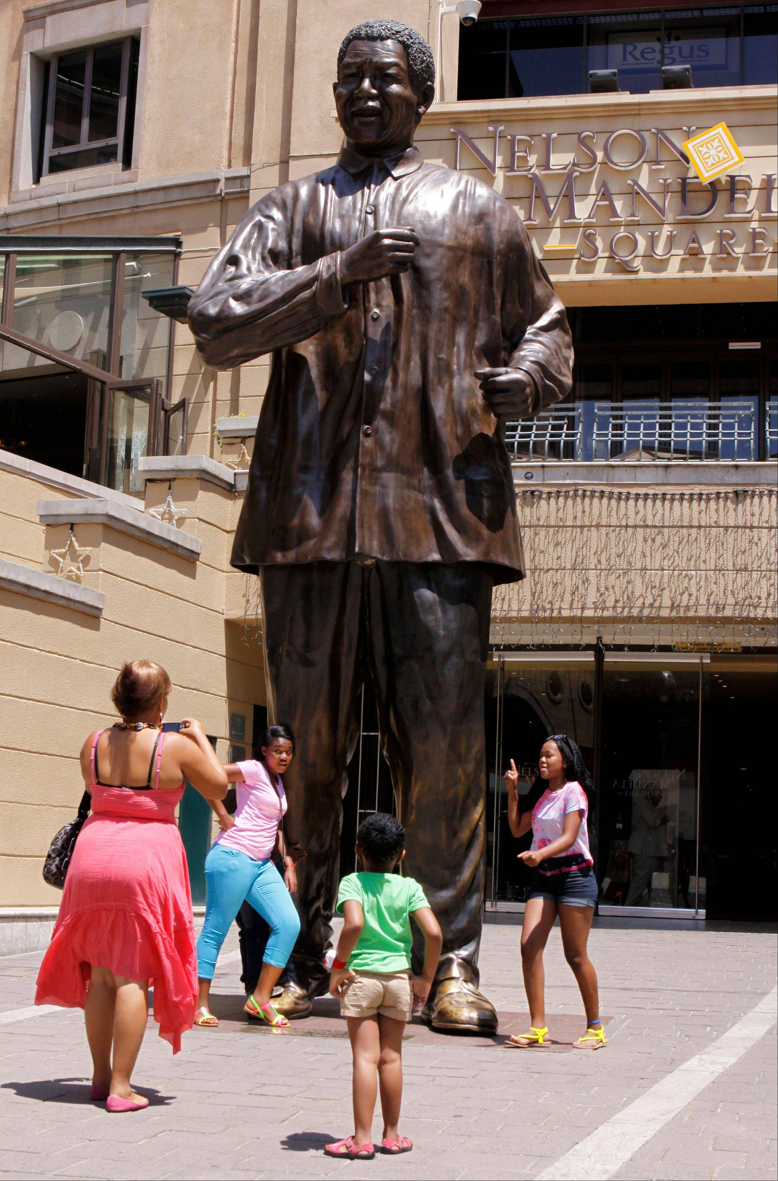 People pose beside the statue of former president Nelson Mandela that overlooks Mandela Square in Johannesburg, South Africa, Sunday. Mandela, 94, is in poor health and hospitalized.