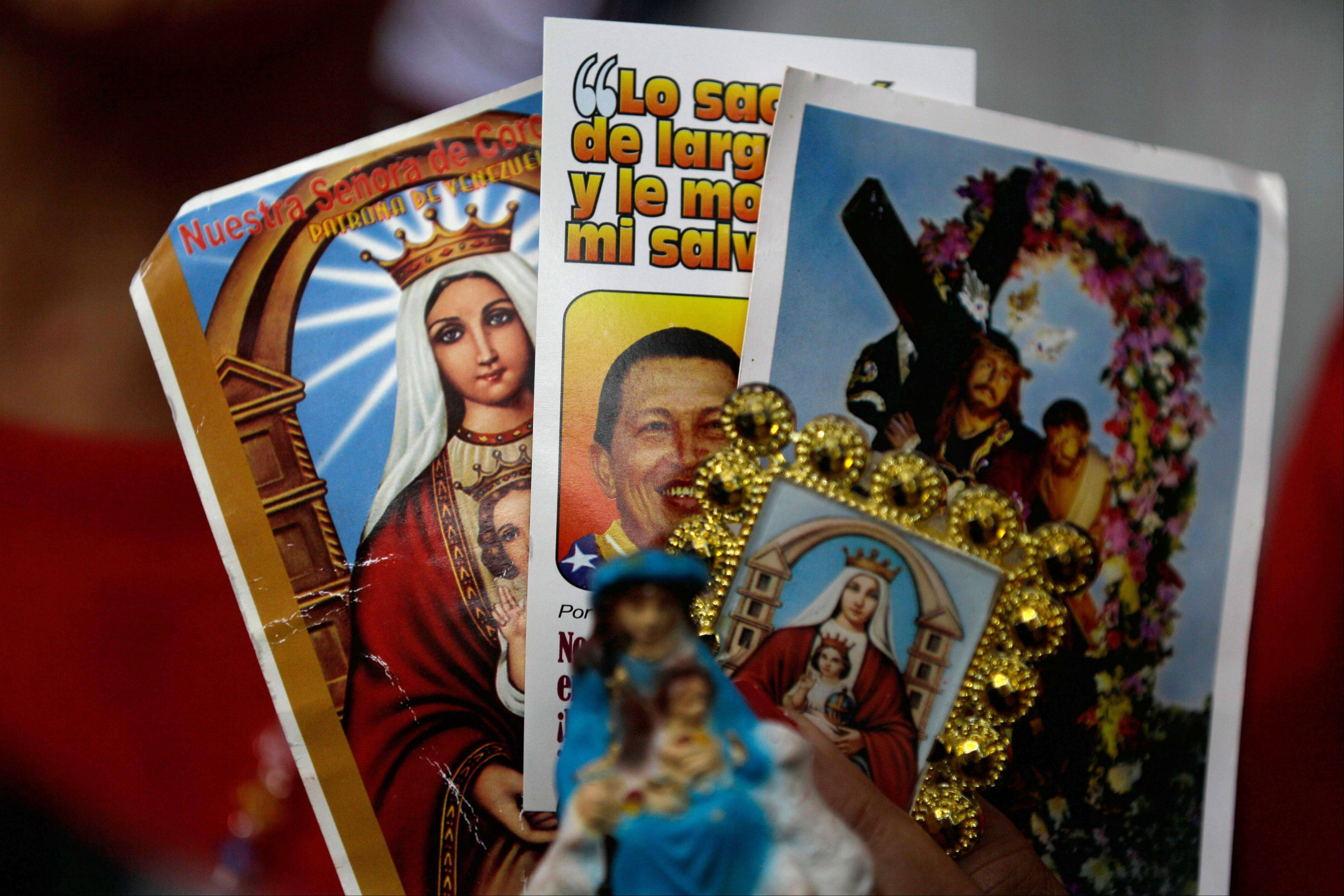 A person holds up an image of Venezuela's President Hugo Chavez among religious images during a demonstration in support of him at the Simon Bolivar square in Caracas, Venezuela, Sunday.