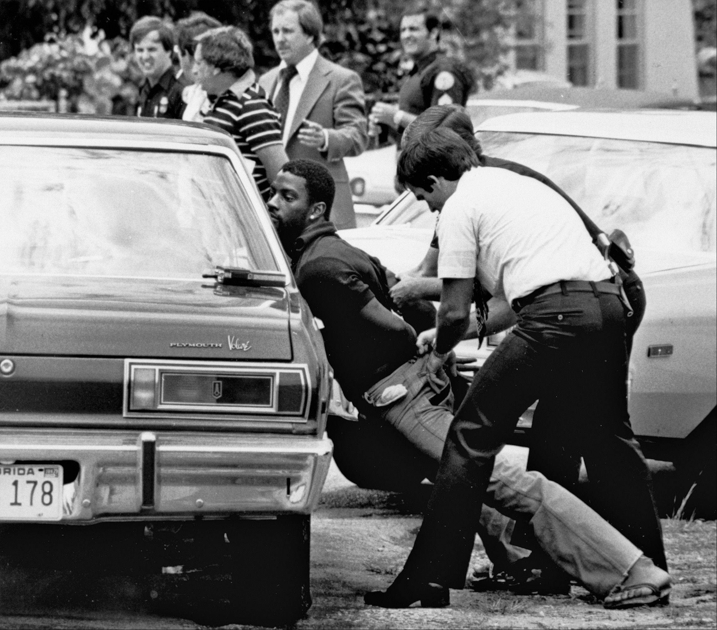 In this 1979 photo, police handcuff a suspect during a drug raid in Miami. Police said eight were arrested and marijuana was seized.