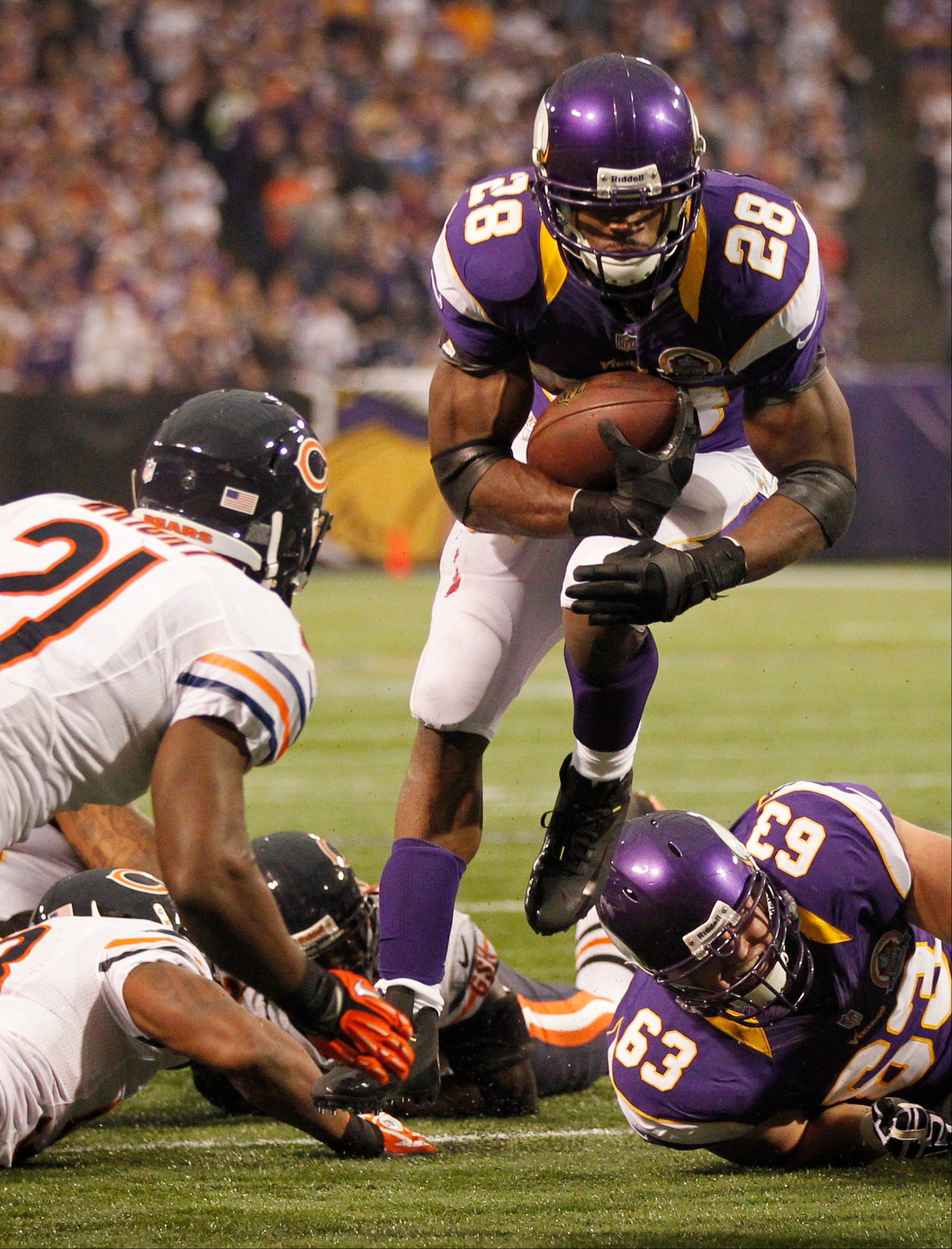 Minnesota Vikings running back Adrian Peterson runs from Chicago Bears safety Major Wright, left, during the first half.