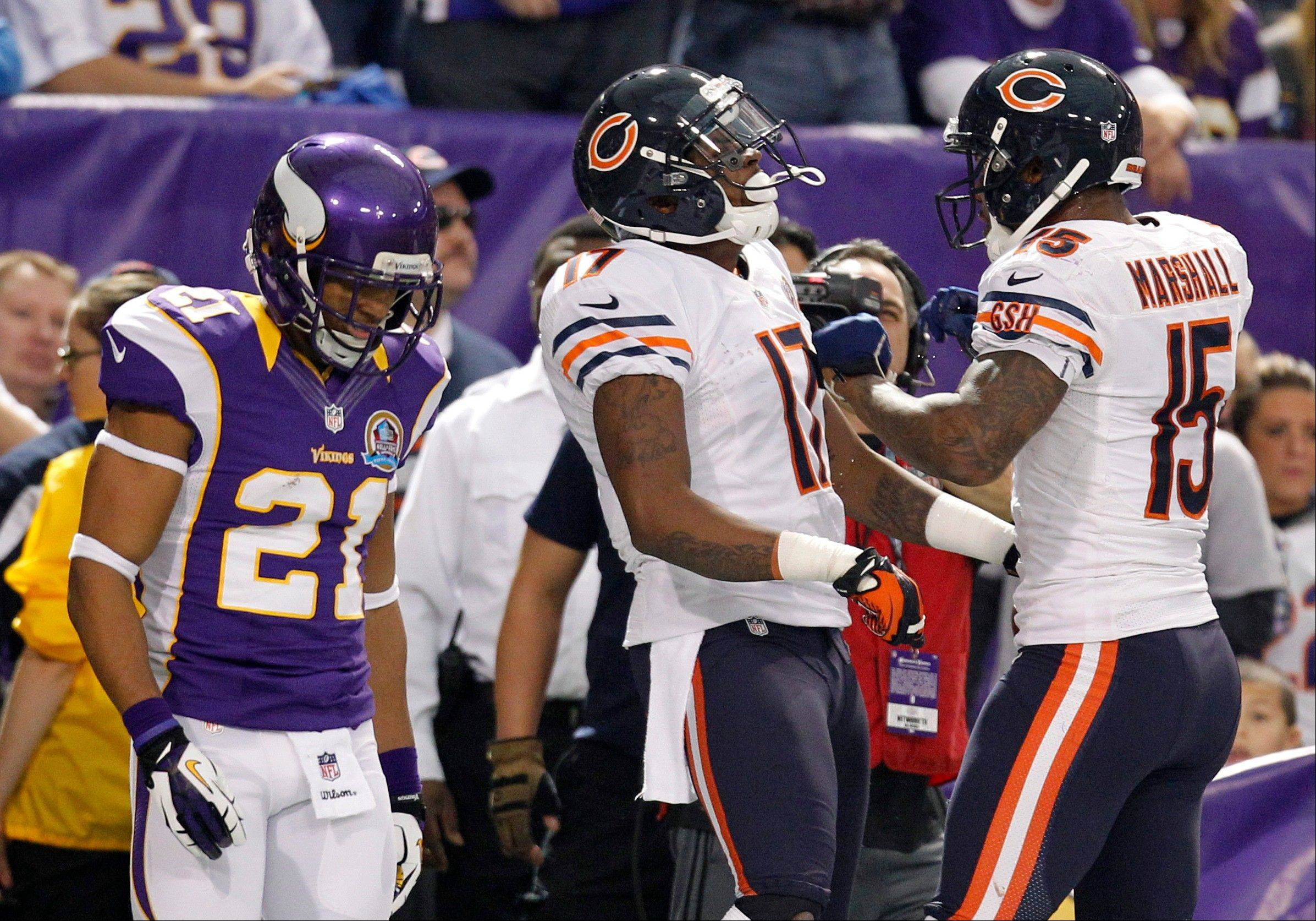 Chicago Bears wide receiver Alshon Jeffery, center, celebrates with teammate Brandon Marshall, right, in front of Minnesota Vikings cornerback Josh Robinson after catching a 23-yard touchdown pass during the first half.