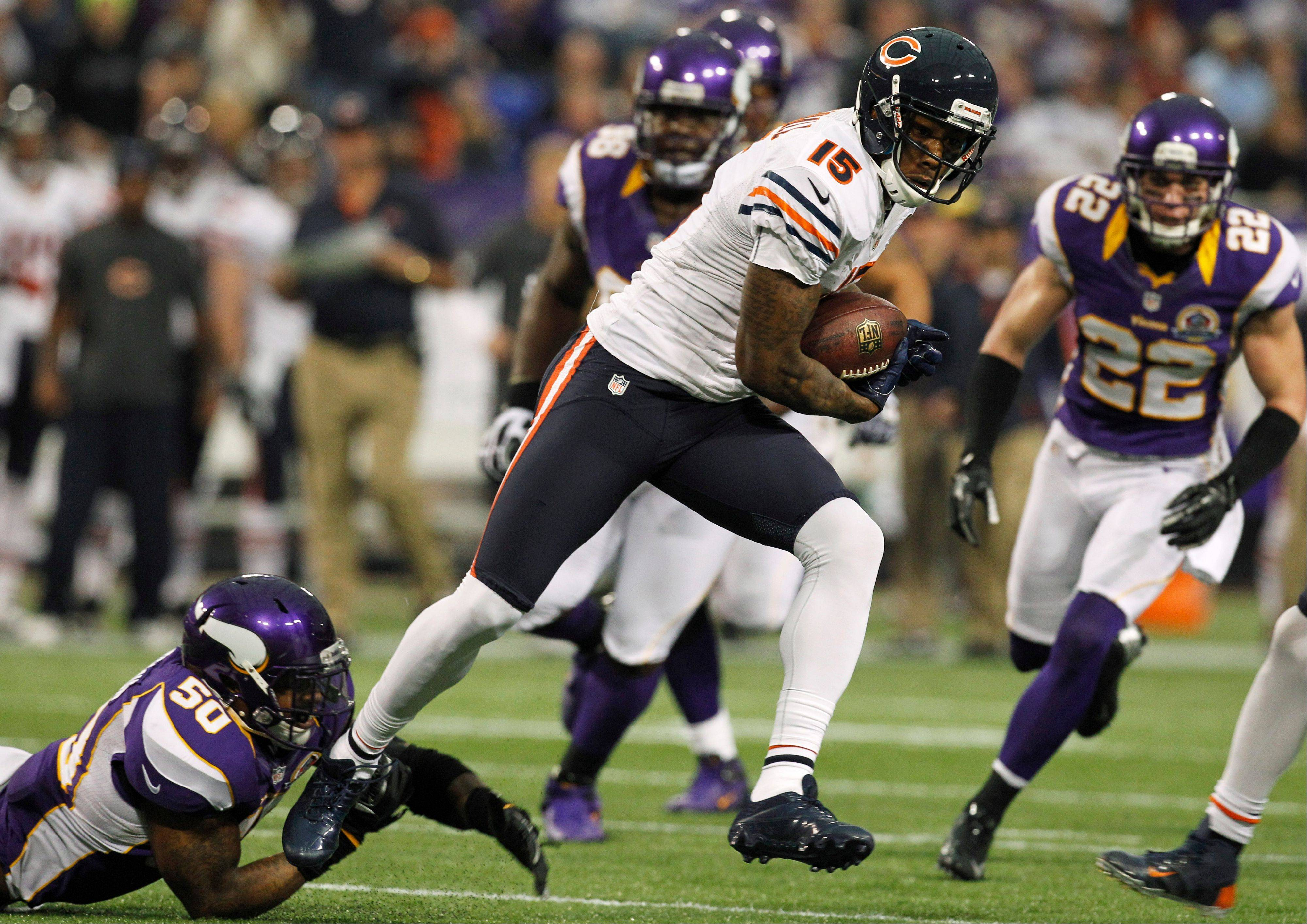 Chicago Bears wide receiver Brandon Marshall tries to break a tackle by Minnesota Vikings linebacker Erin Henderson, left, after making a reception during the first half.