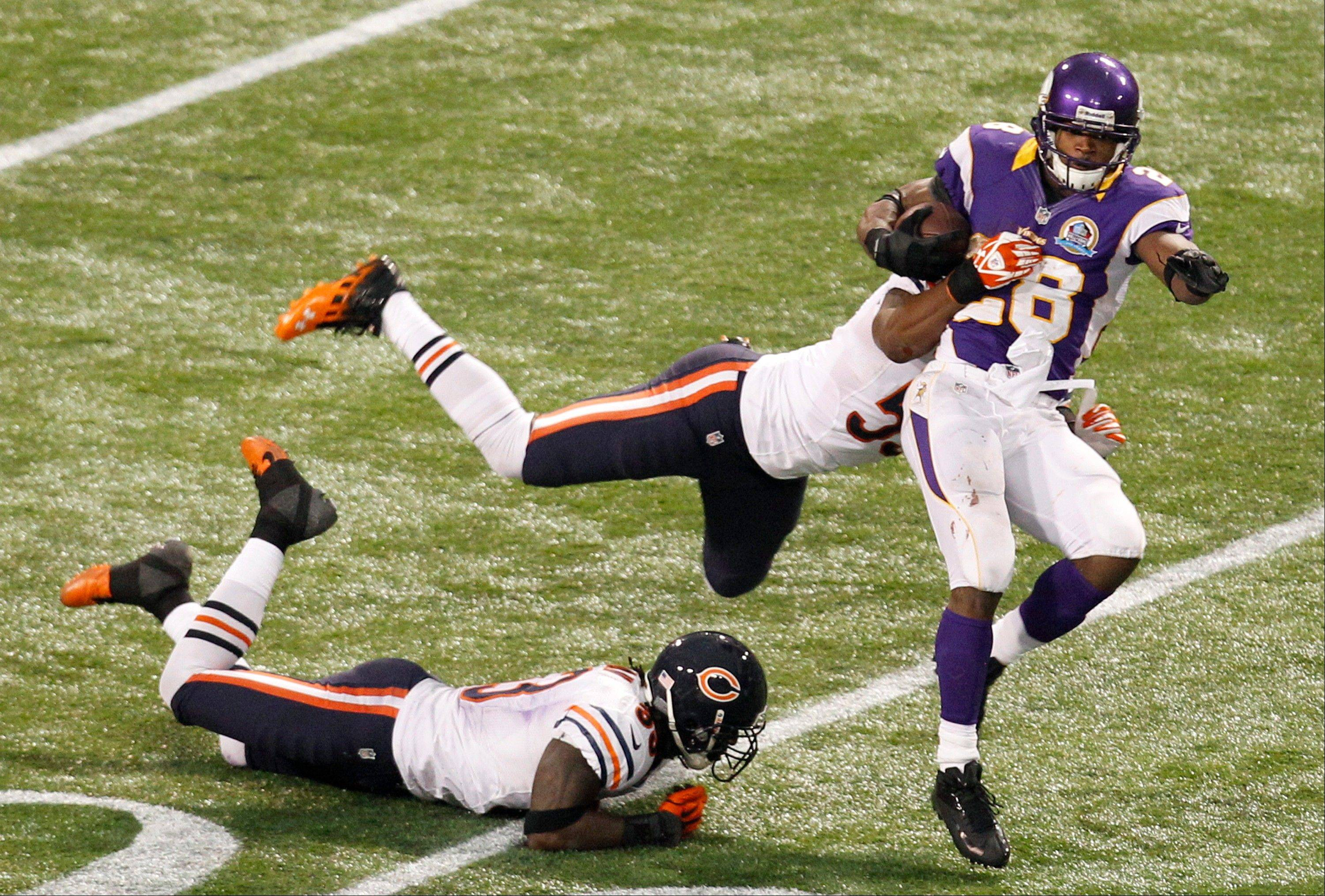 Minnesota Vikings running back Adrian Peterson, right, tries to break a tackle by Chicago Bears linebacker Nick Roach, center, and cornerback Charles Tillman, left, during the second half.